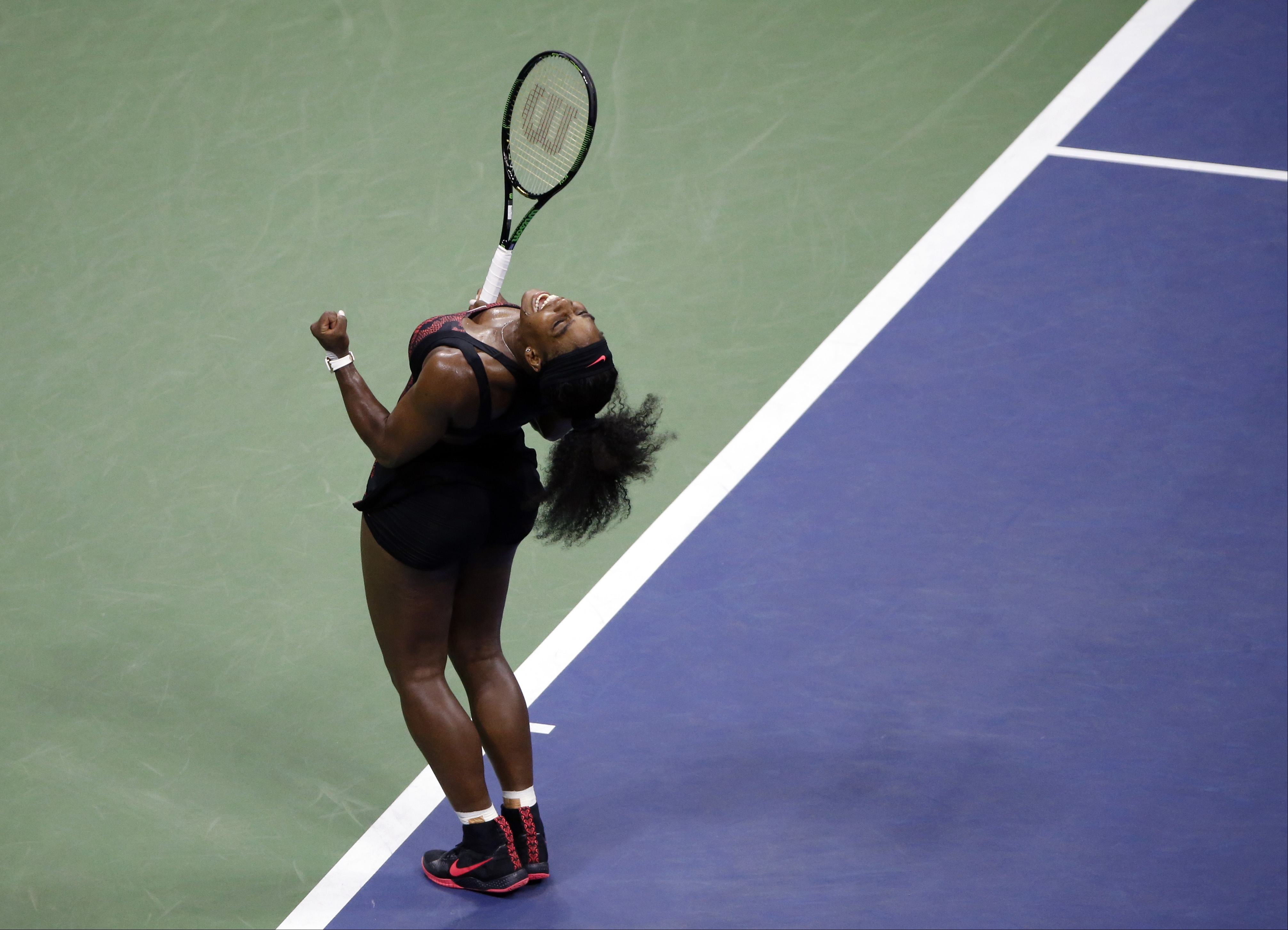 Serena Williams reacts after beating Venus Williams during a quarterfinal match at the U.S. Open tennis tournament, Tuesday, Sept. 8, 2015, in New York. (AP Photo/Jason DeCrow)