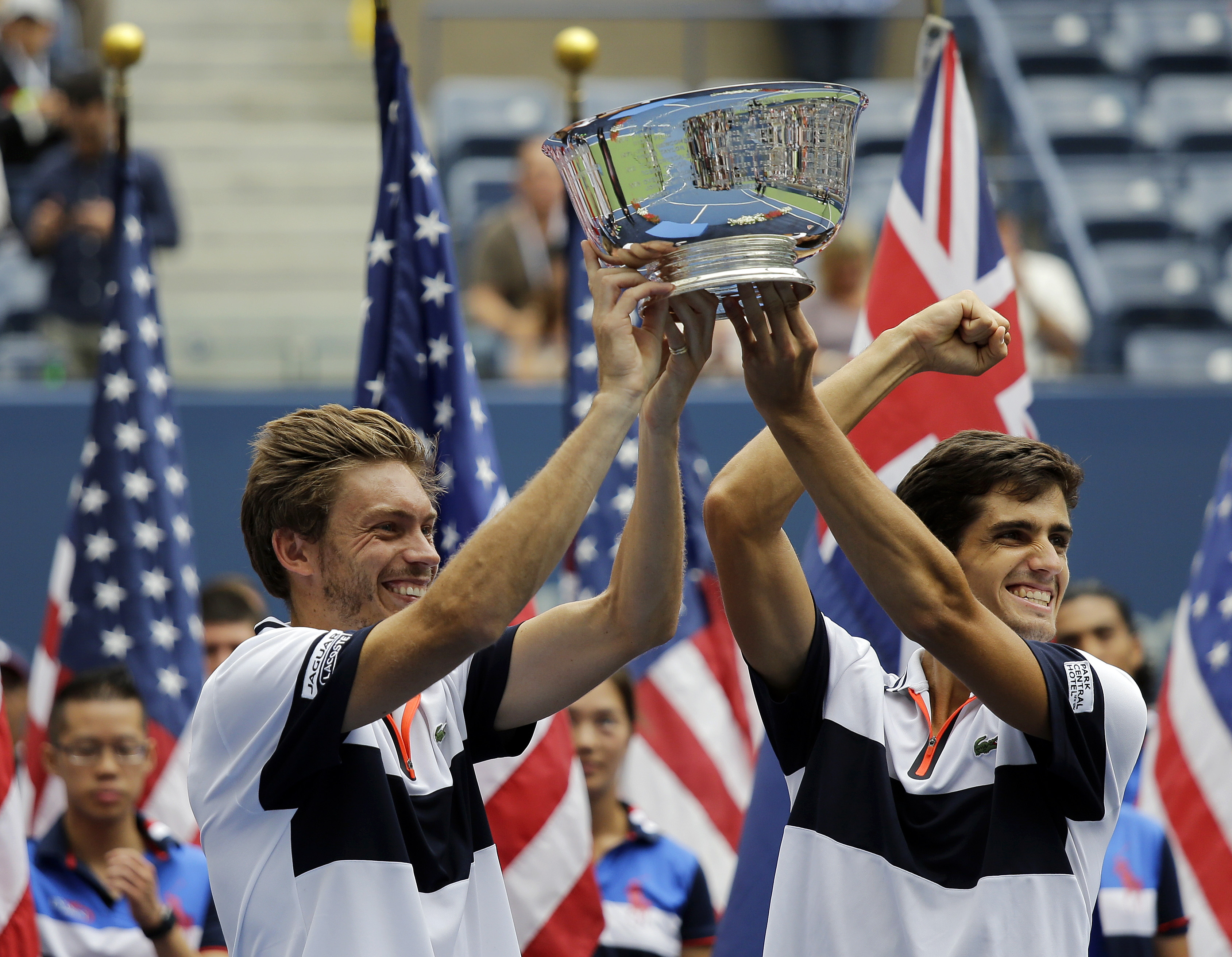 Pierre-Hugues Herbert, right, of France, and Nicolas Mahut, of France, hold up the men's doubles championship trophy after beating John Peers, of Australia, and Jamie Murray, of the United Kingdom, in the men's doubles final at the U.S. Open tennis tourna