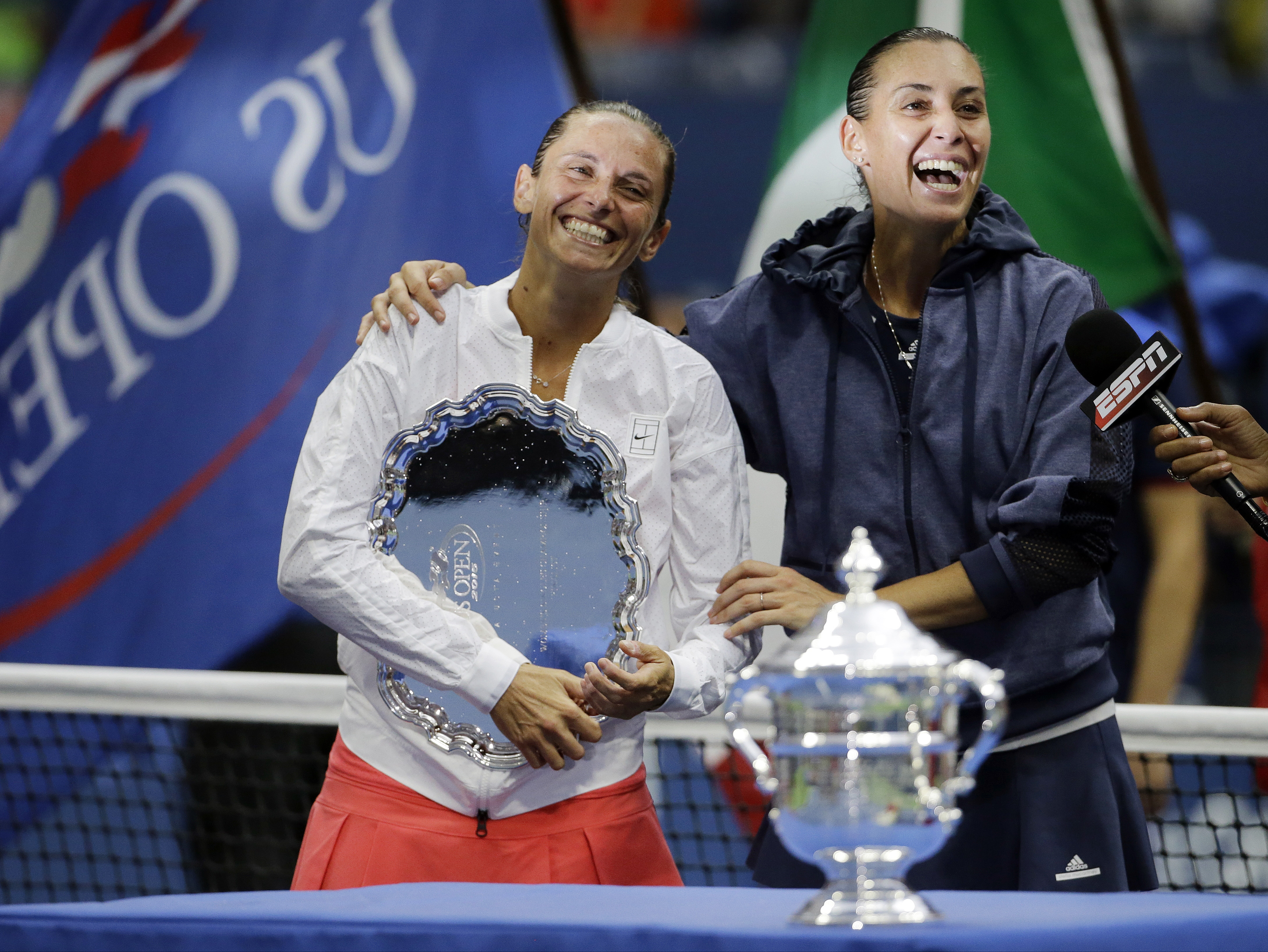 Roberta Vinci, of Italy, left, and Flavia Pennetta, of Italy, react during the trophy ceremony for the women's championship match of the U.S. Open tennis tournament, Saturday, Sept. 12, 2015, in New York. Pennetta beat Vinci in straight sets. (AP Photo/Da