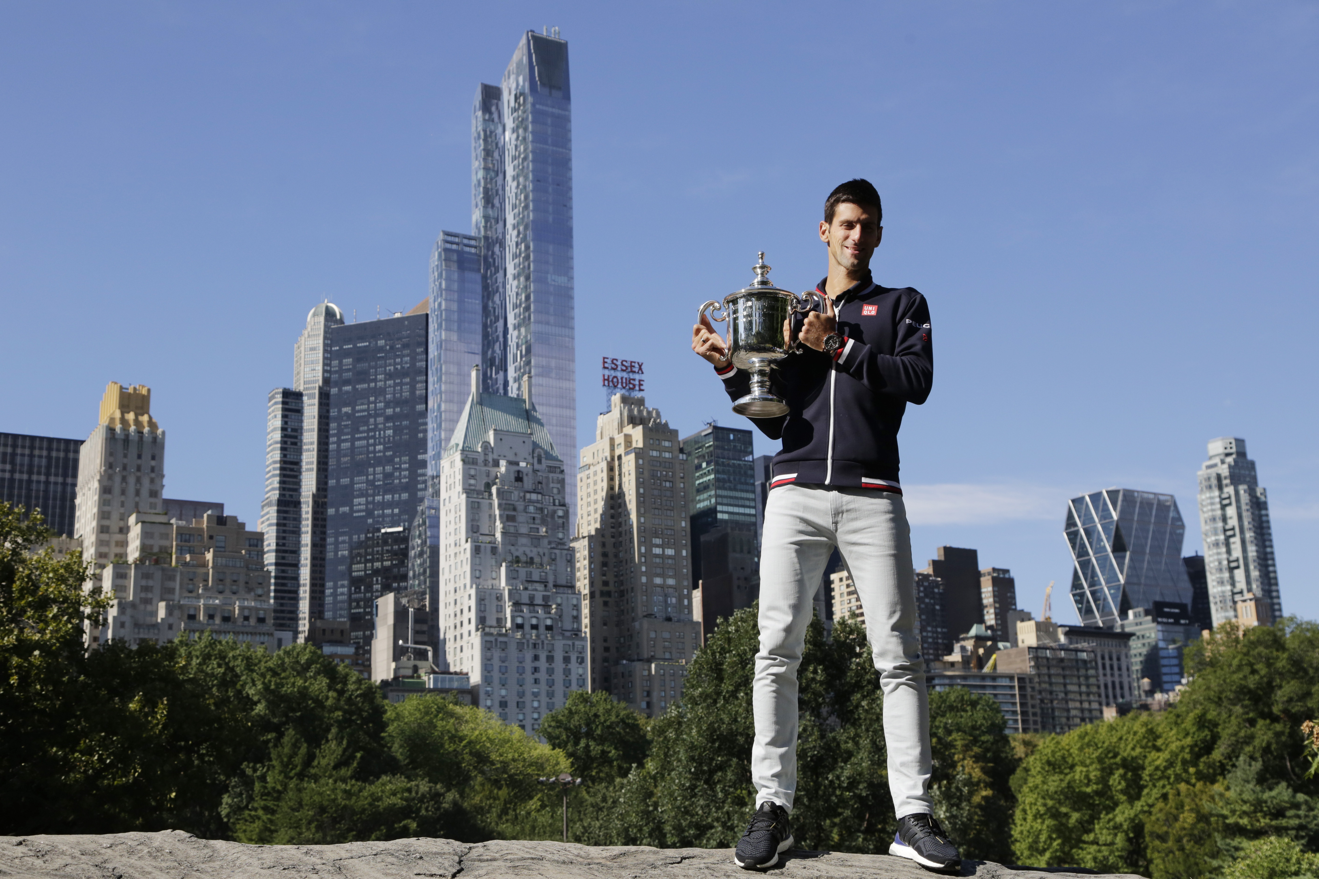 Novak Djokovic poses with the U.S. Open tennis championship trophy, Monday, Sept. 14, 2015, in New York's Central Park. Djokovic defeated Roger Federer 6-4, 5-7, 6-4, 6-4 on Sunday, to earn his second U.S. Open title, third major championship of the year