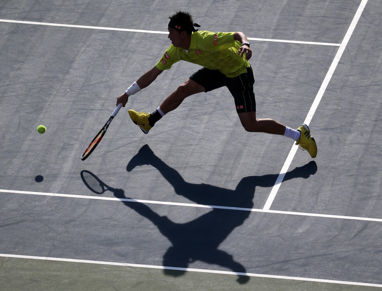 Kei Nishikori of Japan returns a shot against Marin Cilic, of Croatia during their singles quarterfinal match at the Japan Open men's tennis tournament in Tokyo, Friday, Oct. 9, 2015. (AP Photo/Eugene Hoshiko)