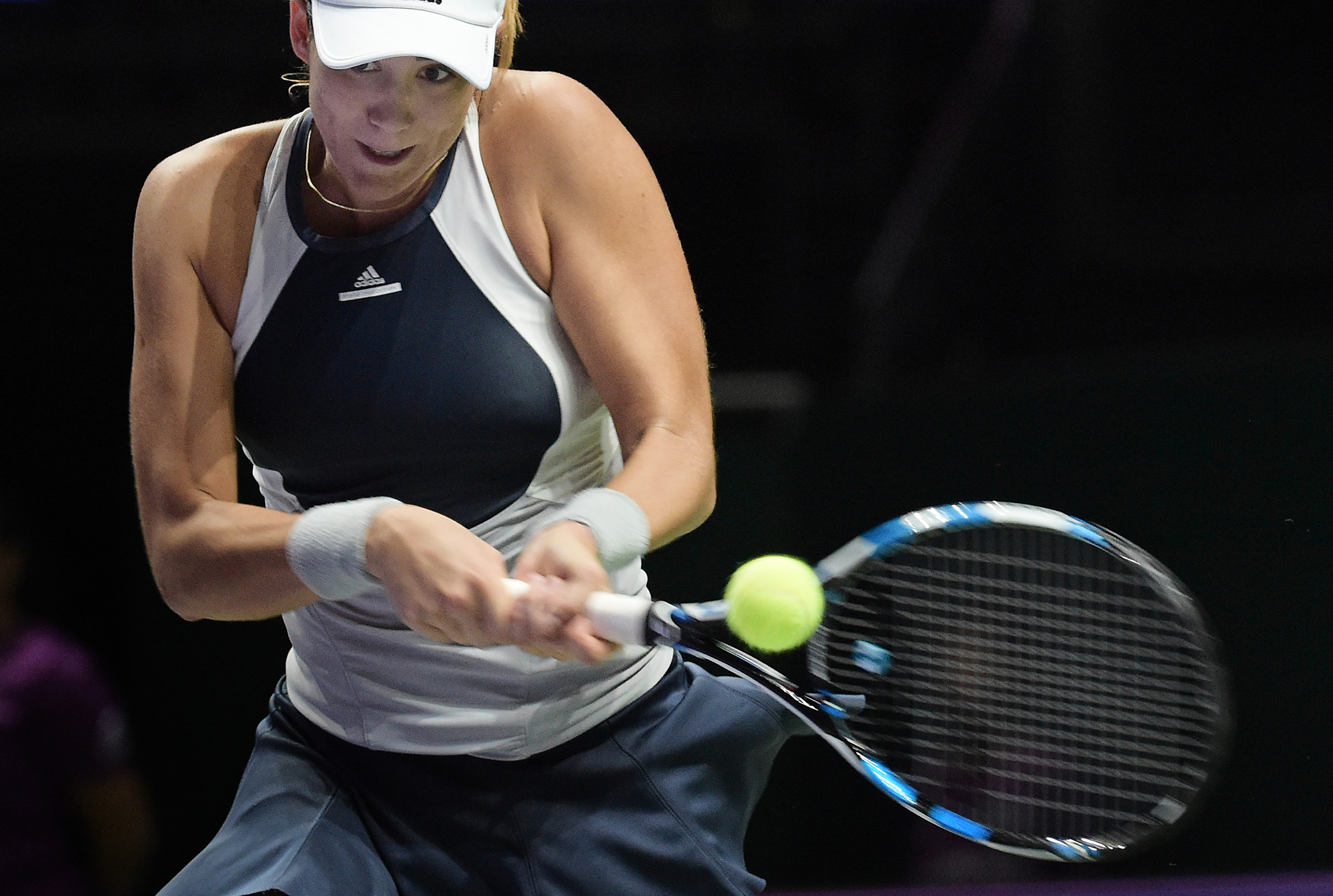 Garbine Muguruza of Spain makes a backhand return against Petra Kvitova of the Czech Republic during their singles match at the WTA tennis finals in Singapore on Friday, Oct. 30, 2015.  (AP Photo/Joseph Nair)