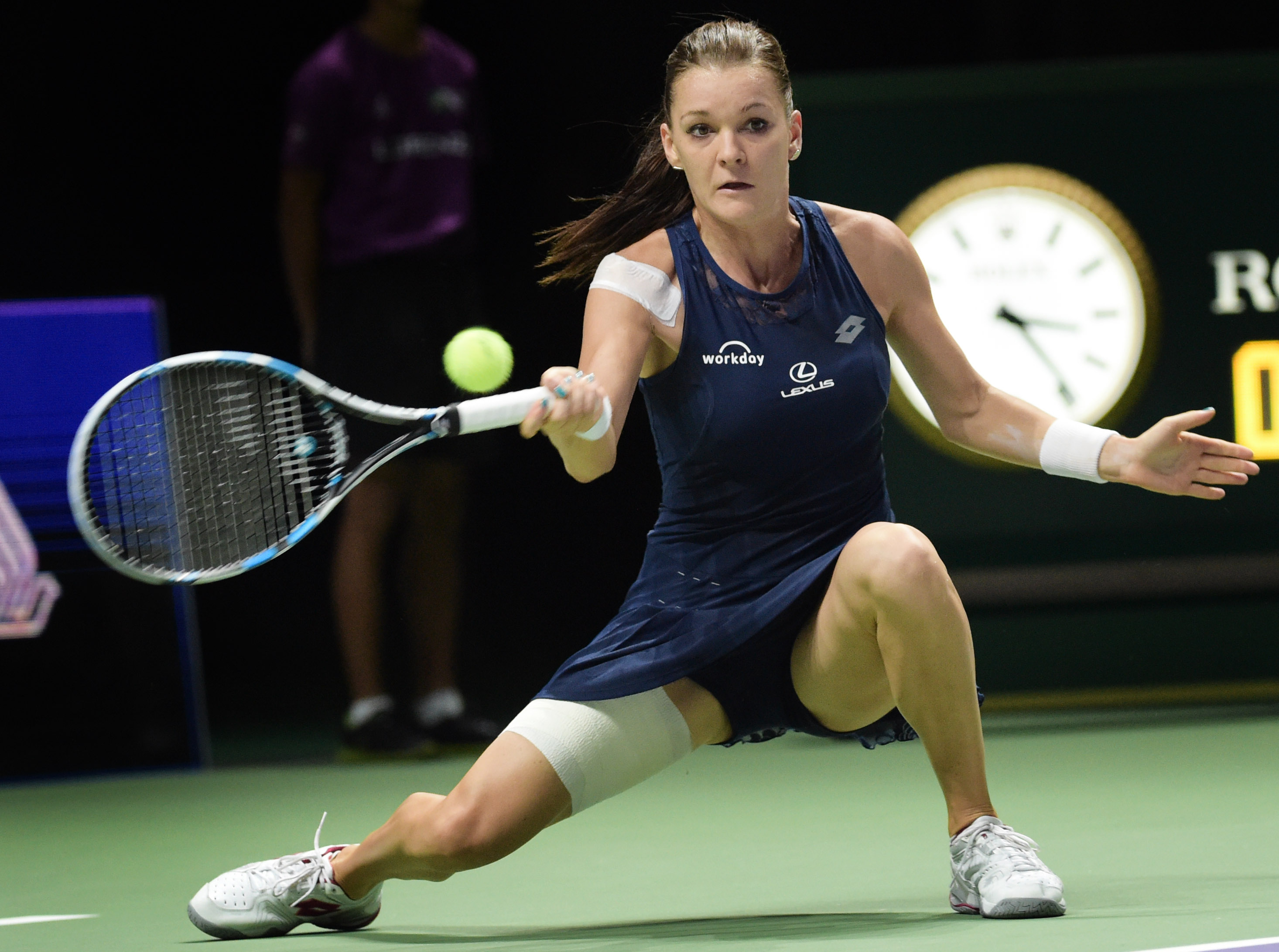 Agnieszka Radwanska of Poland makes a forehand return against Garbine Muguruza of Spain during the singles semifinal at the WTA tennis finals in Singapore on Saturday, Oct. 31, 2015.  (AP Photo/Joseph Nair)