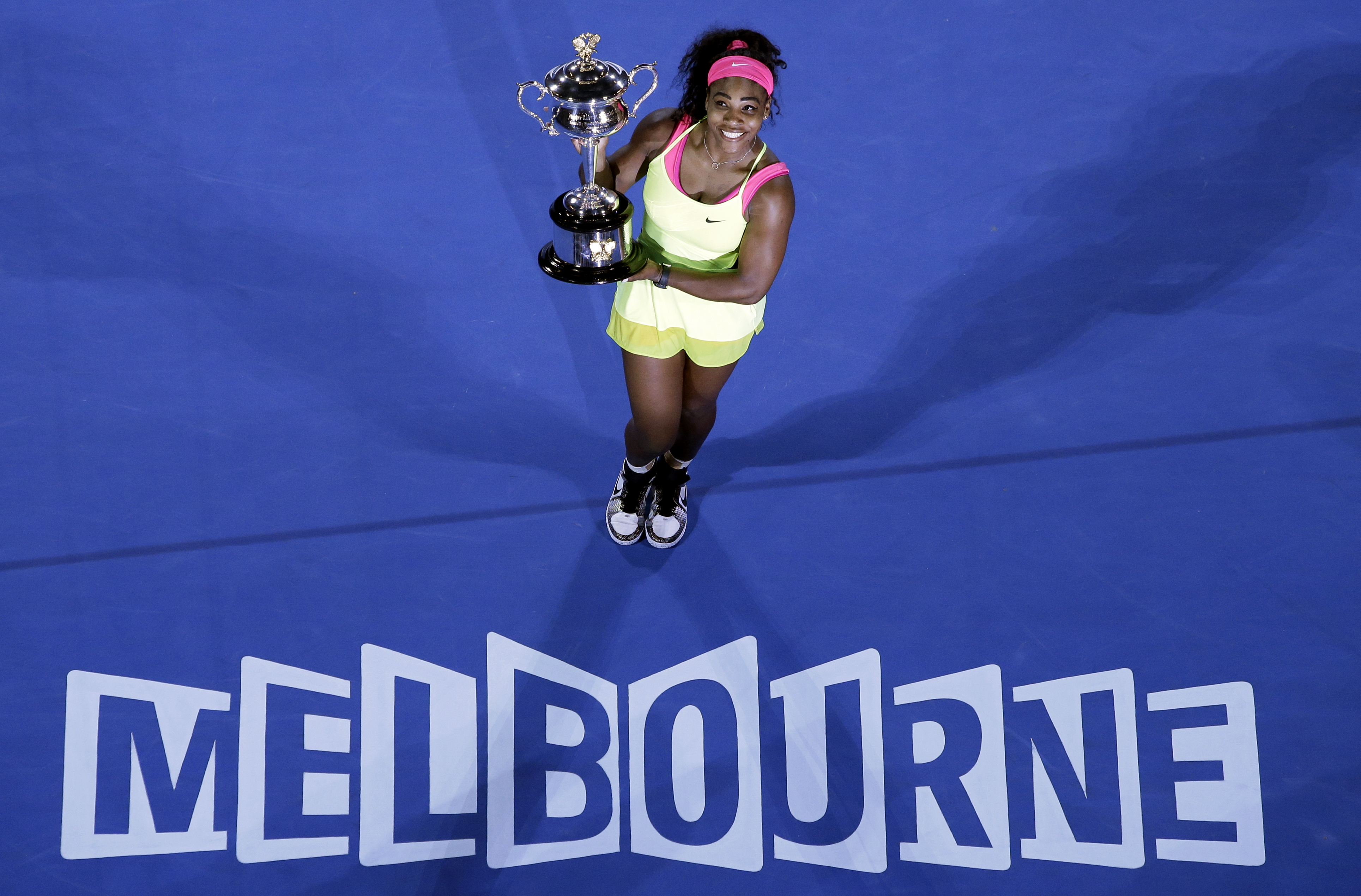 Serena Williams of the U.S. holds the trophy after defeating Maria Sharapova of Russia in the women's singles final at the Australian Open tennis championship in Melbourne, Australia, Saturday, Jan. 31, 2015. (AP Photo/Lee Jin-man)