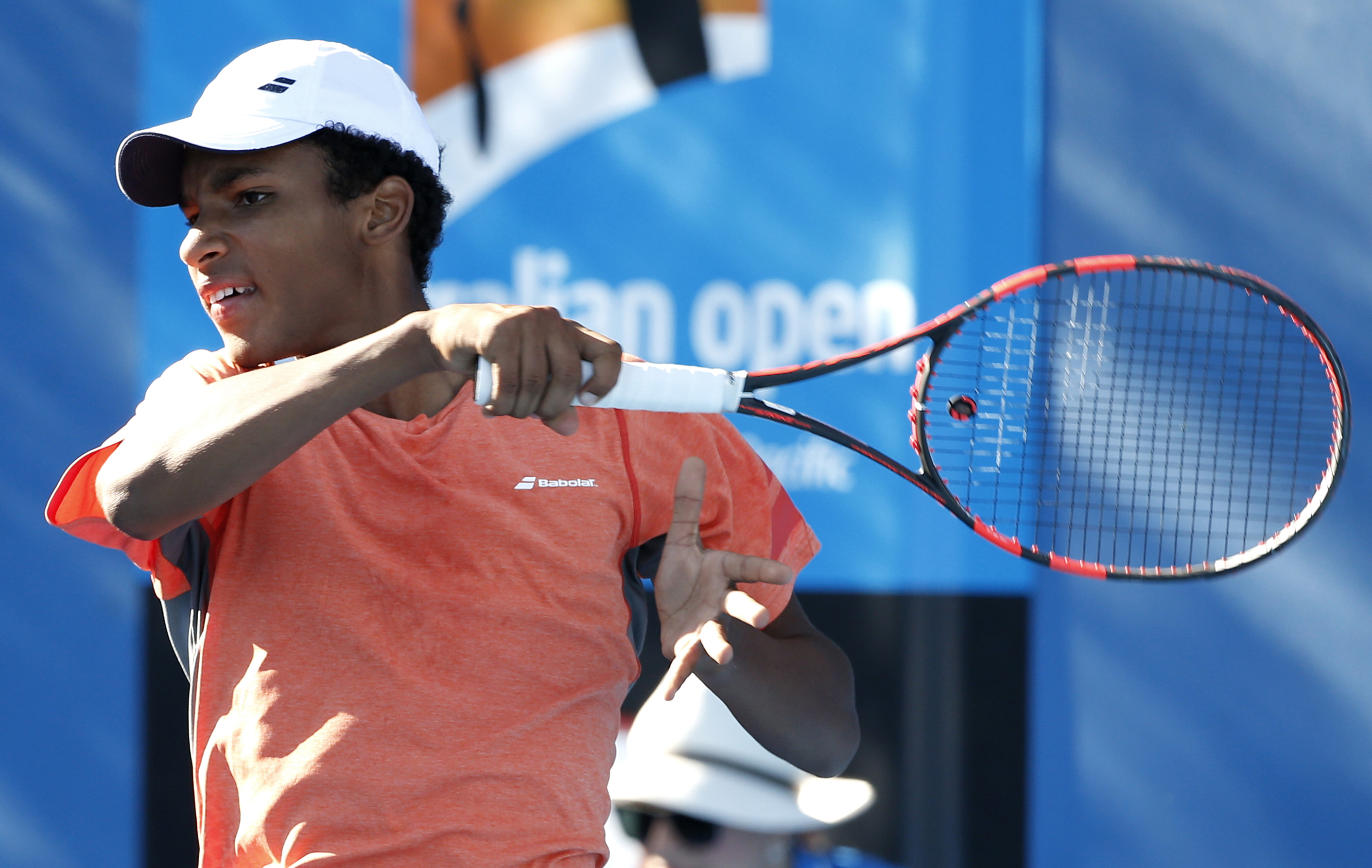 In this Sunday Jan. 24, 2016 photo Canada's junior tennis player Felix Auger Aliassime plays a forehand return during his singles match against Italy's Andres Gabriel Ciurletti at the Australian Open tennis championships in Melbourne. Growing up in Quebec