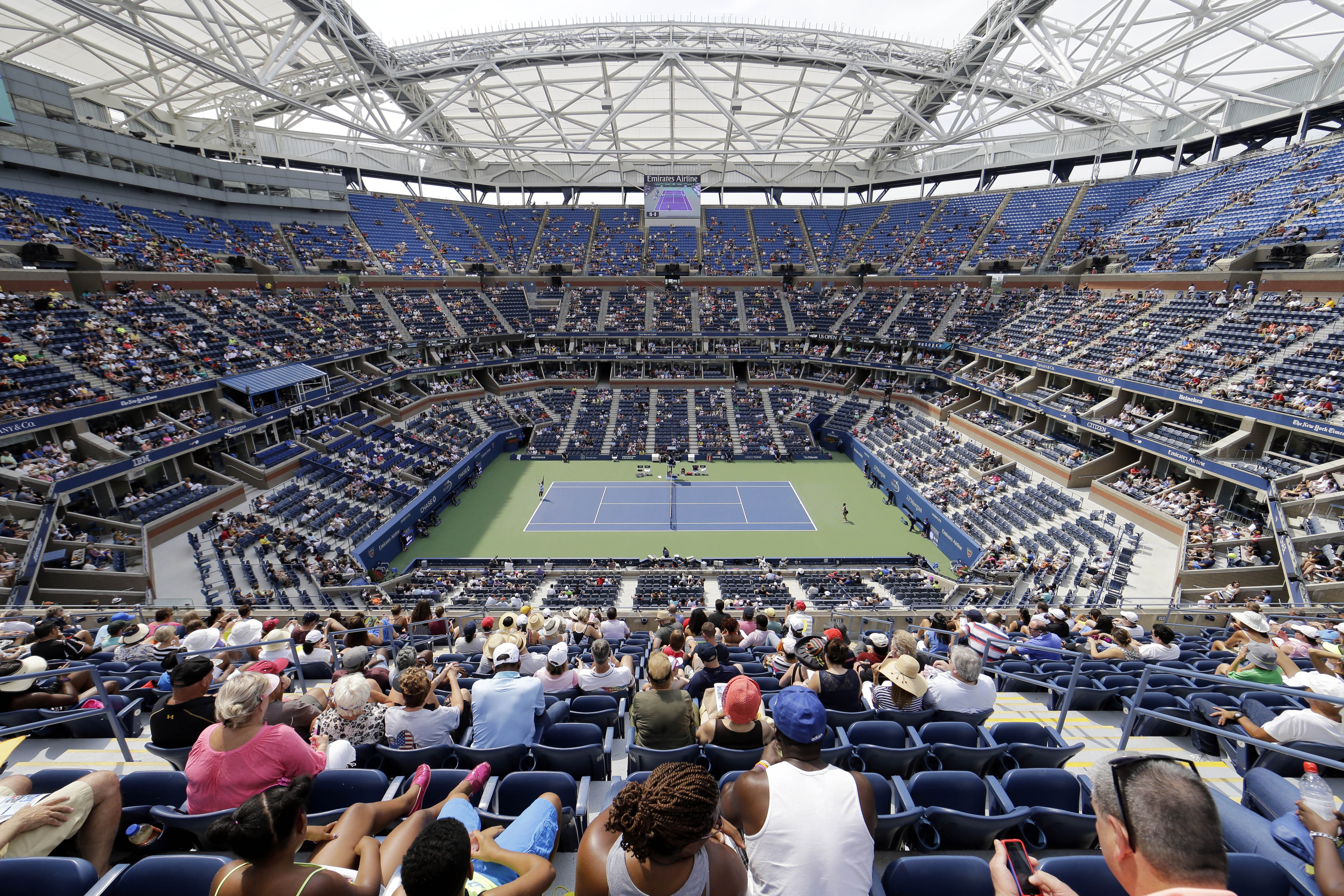 Tennis fans watch play during the first round of the U.S. Open tennis tournament under the frame of the uncompleted roof over Arthur Ashe Stadium, Monday, Aug. 31, 2015, in New York. (AP Photo/Matt Rourke)