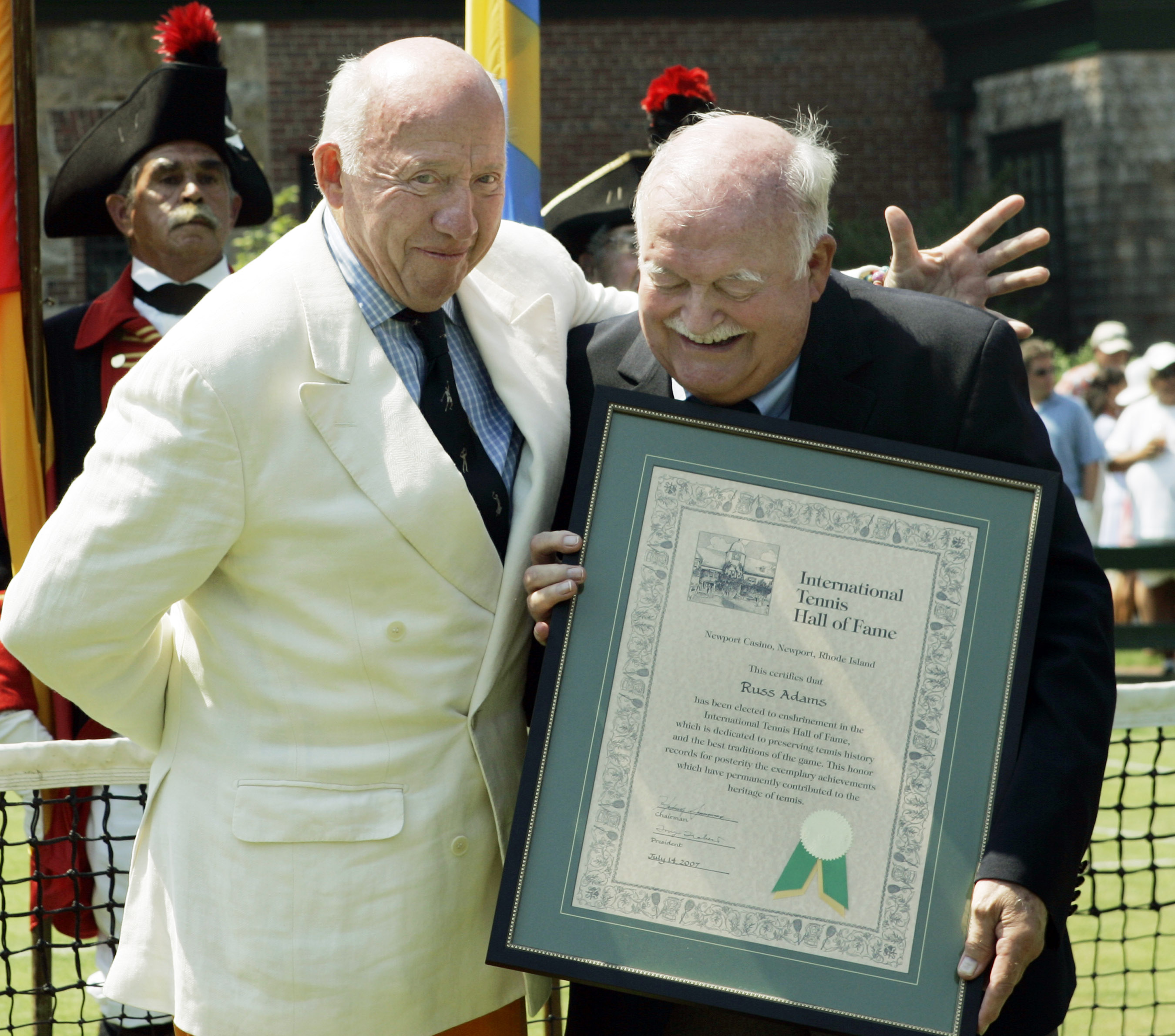 Presenter Bud Collins, left, puts his arm around photographer Russ Adams as they pose for photos after Adams' induction into the International Tennis Hall of Fame in Newport, R.I. Saturday, July 14, 2007. (AP Photo/Elise Amendola)