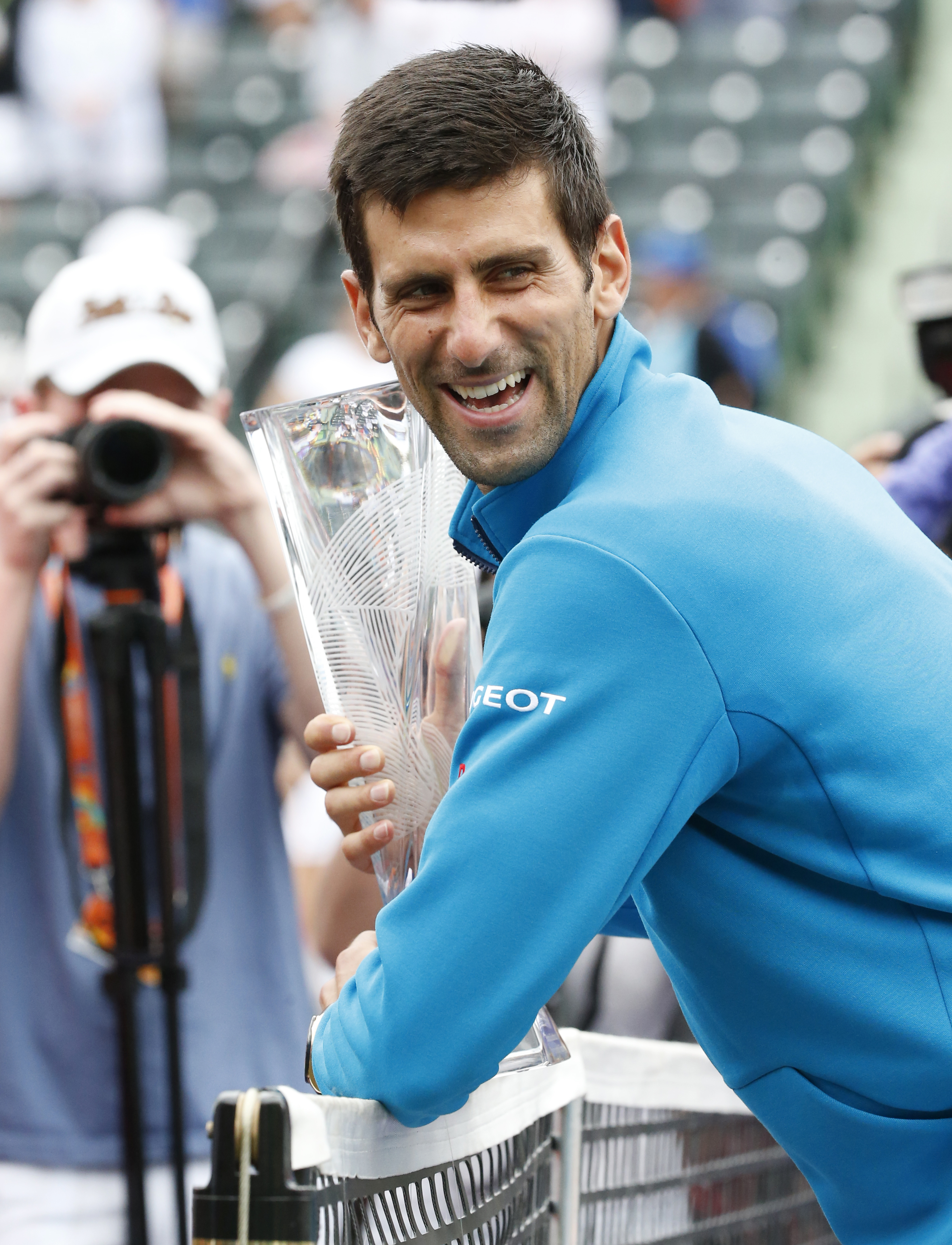 Novak Djokovic, of Serbia, smiles as he poses for photos after defeating Kei Nishikori, of Japan, 6-3, 6-3, during the men's singles final match at the Miami Open tennis tournament, Sunday, April 3, 2016, in Key Biscayne, Fla. (AP Photo/Wilfredo Lee)