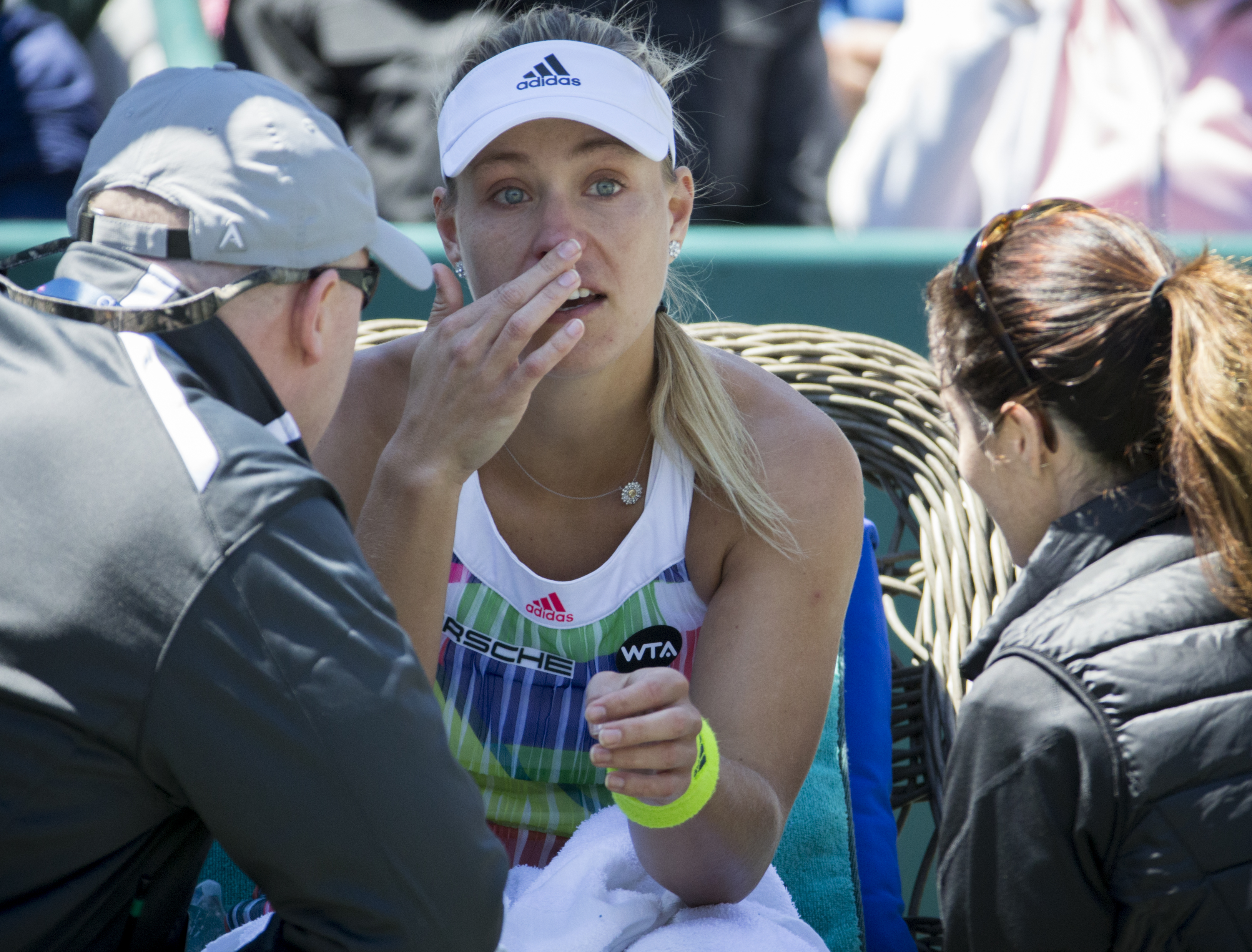 Angelique Kerber of Germany, talks with trainers during a timeout in her tennis match against Sloane Stephens in the semifinals at the Volvo Car Open in Charleston, S.C., Saturday, April 9, 2016. Kerber retired in the second set. (AP Photo/Stephen B. Mort