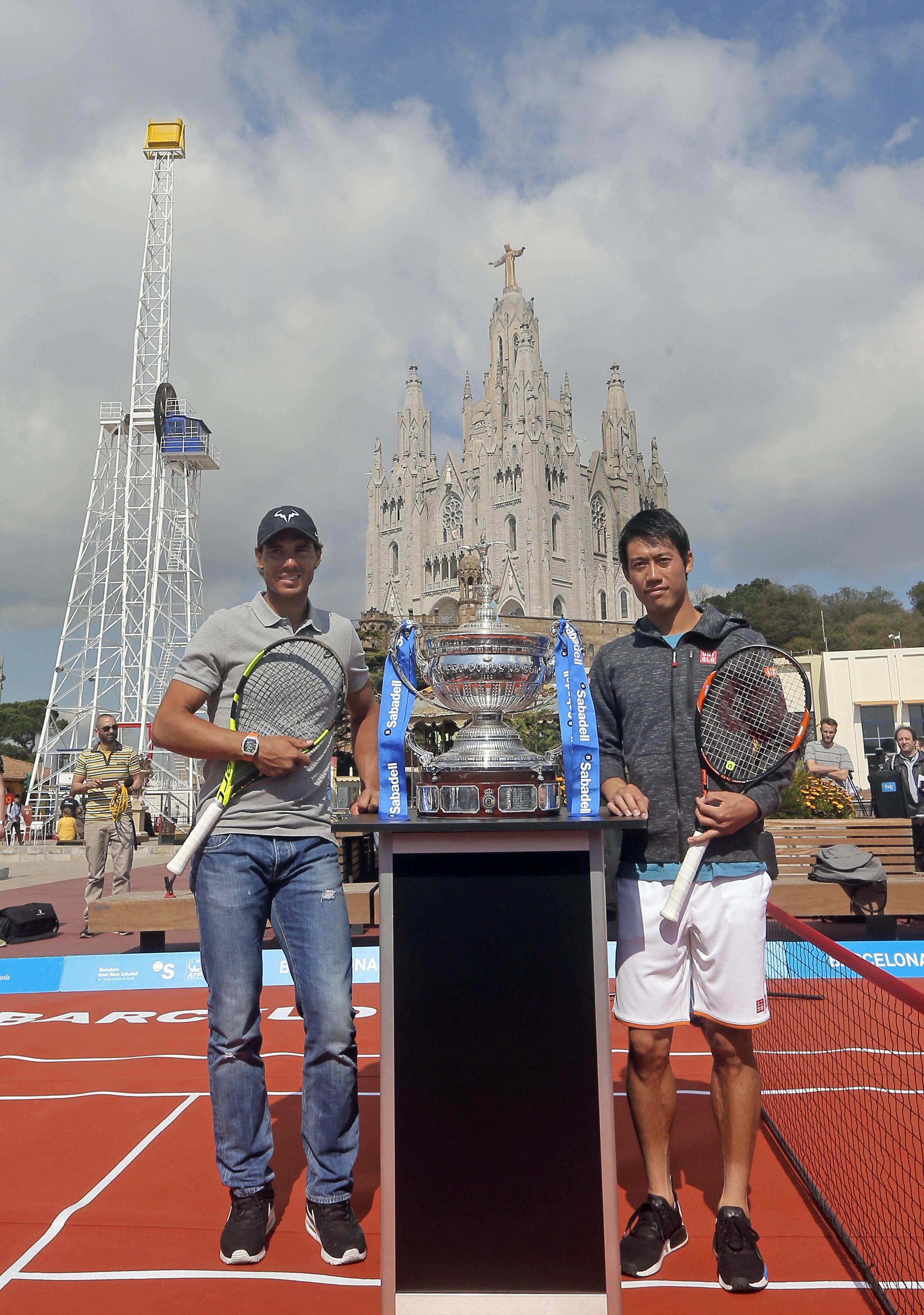 Spain's Rafael Nadal, left, and Kei Nishikori, of Japan pose for the media with the Barcelona Open trophy ahead of the Barcelona Open tennis tournament at the Tibidabo park in Barcelona, Spain, Monday, April 18, 2016. The week-long Barcelona Open tennis t