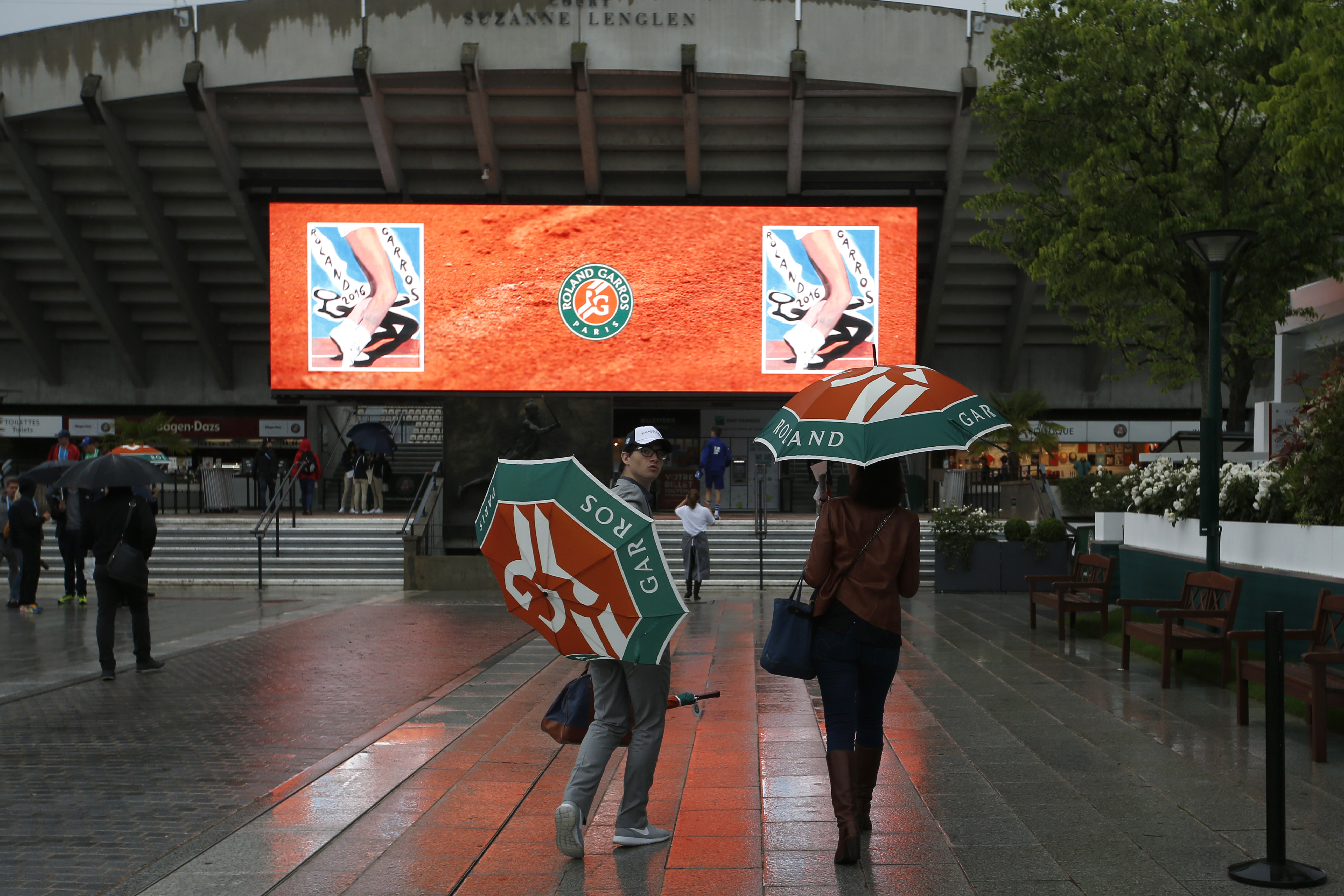 People stroll under umbrellas in the alleys of the Roland Garros stadium before the first round matches of the French Open tennis tournament, Sunday, May 22, 2016 in Paris.  (AP Photo/Alastair Grant)