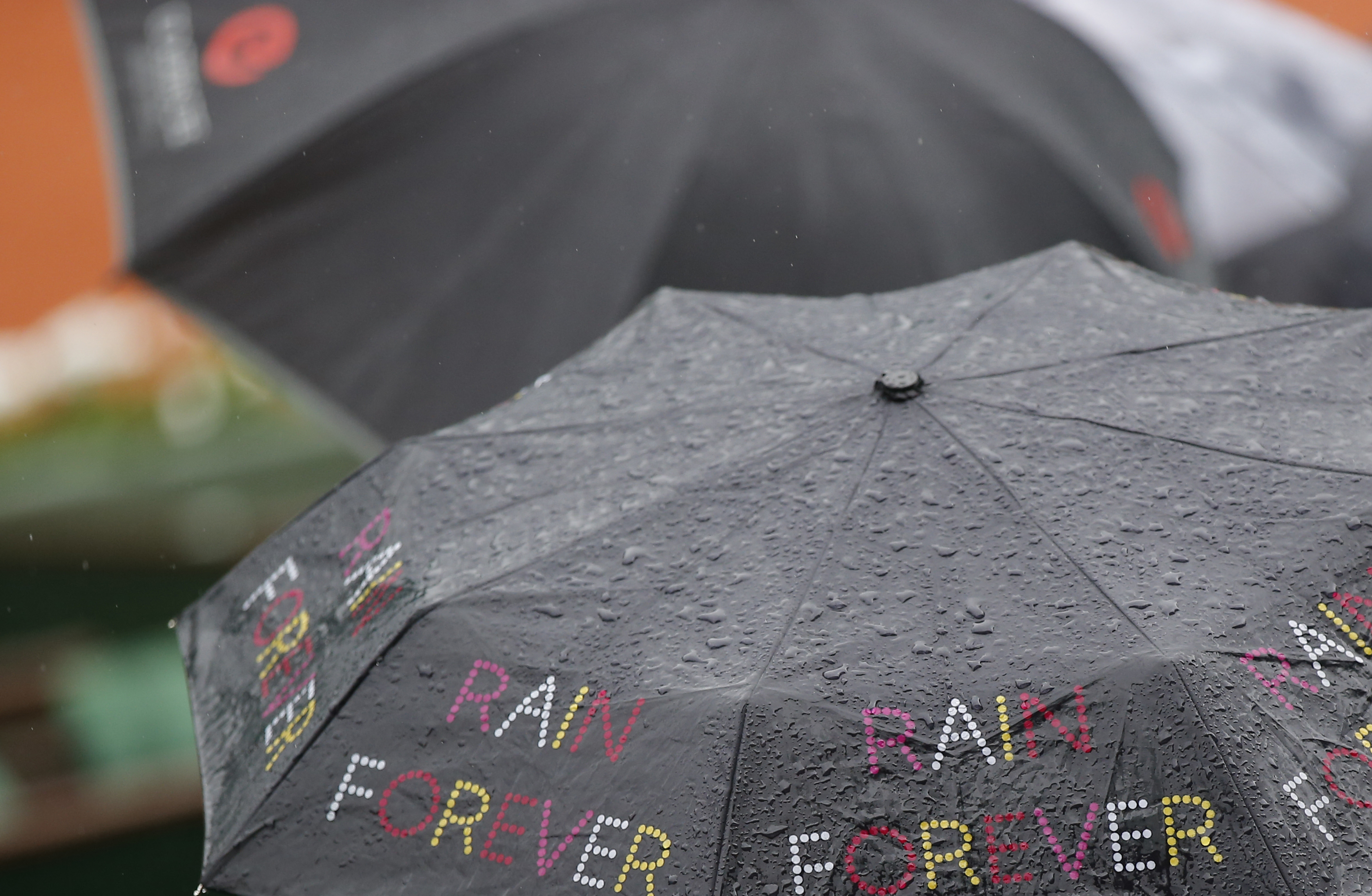 """Spectators sit under an umbrella reading """"Rain Forever"""" shortly before all first round matches of the French Open tennis tournament were delayed till the next day because of the rain at Roland Garros stadium in Paris, France, Sunday, May 22, 2016. (AP Pho"""