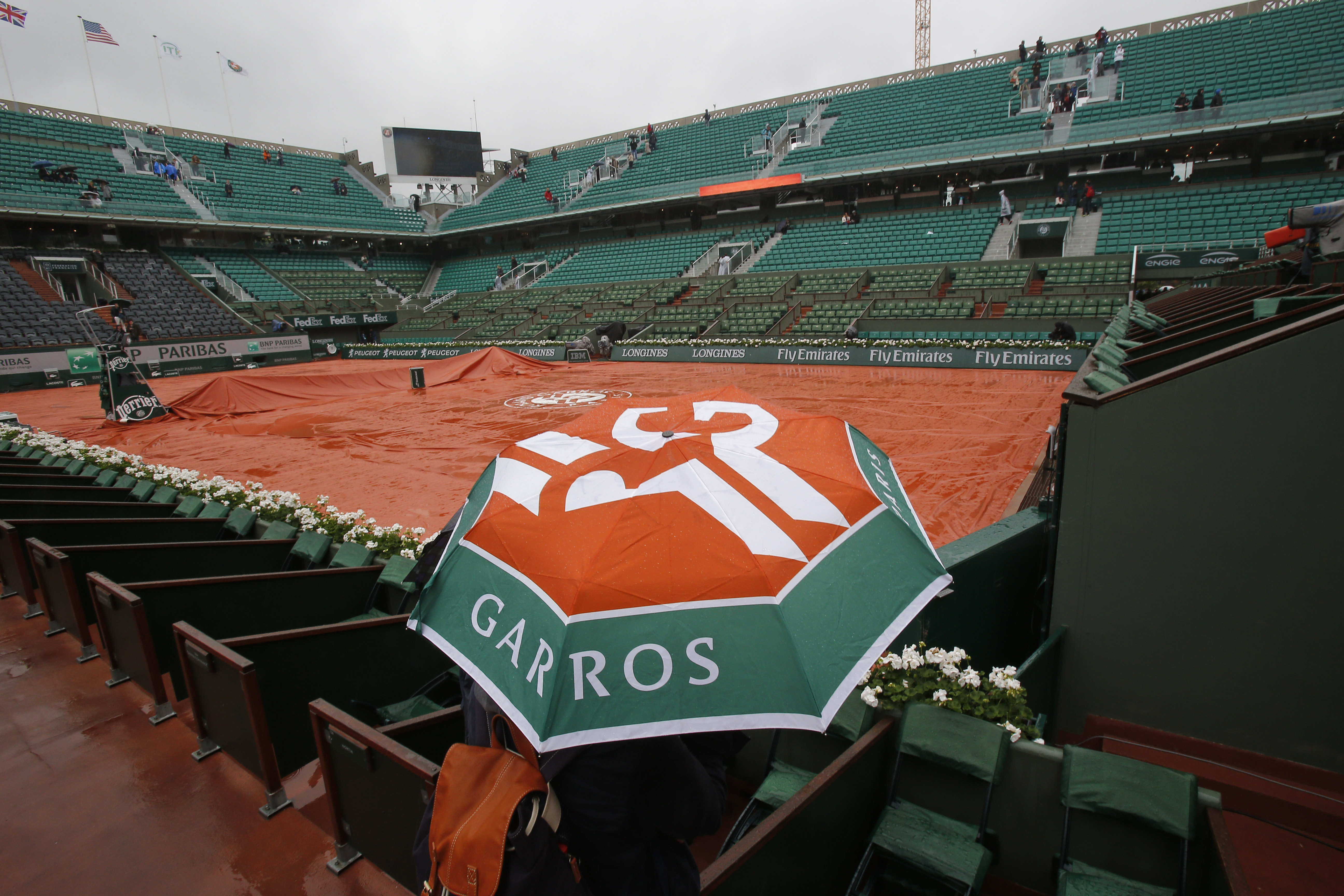 A few spectators wander around on center court of the French Open tennis tournament at the Roland Garros stadium in Paris, France, Monday, May 30, 2016. French Open organizers have announced the cancellation of all matches Monday at Roland Garros because