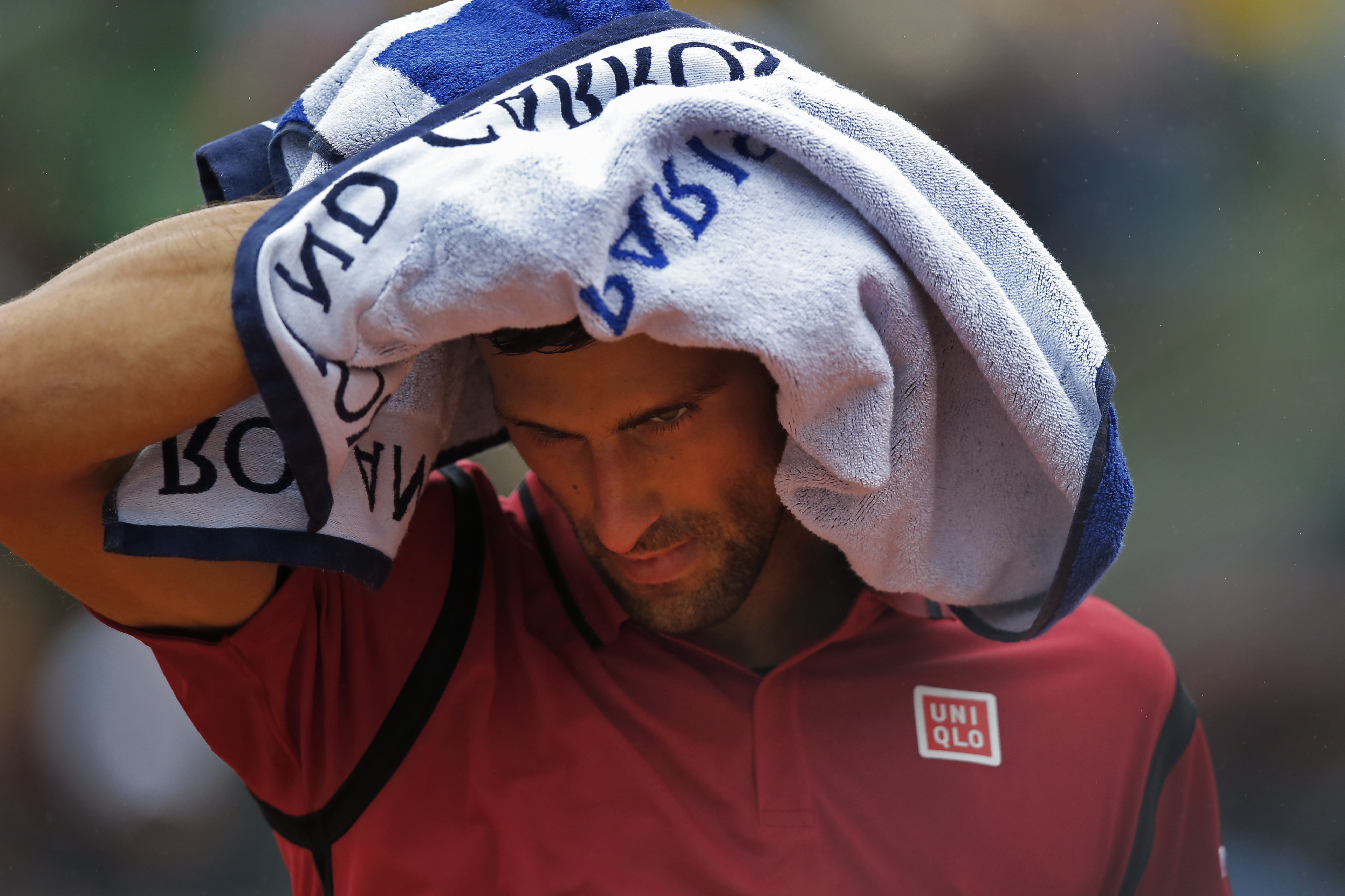 Serbia's Novak Djokovic covers his head minutes before the fourth round match of the French Open tennis tournament against Spains Roberto Bautista Agut was suspended for the second time because of the rain at the Roland Garros stadium in Paris, France, Tu