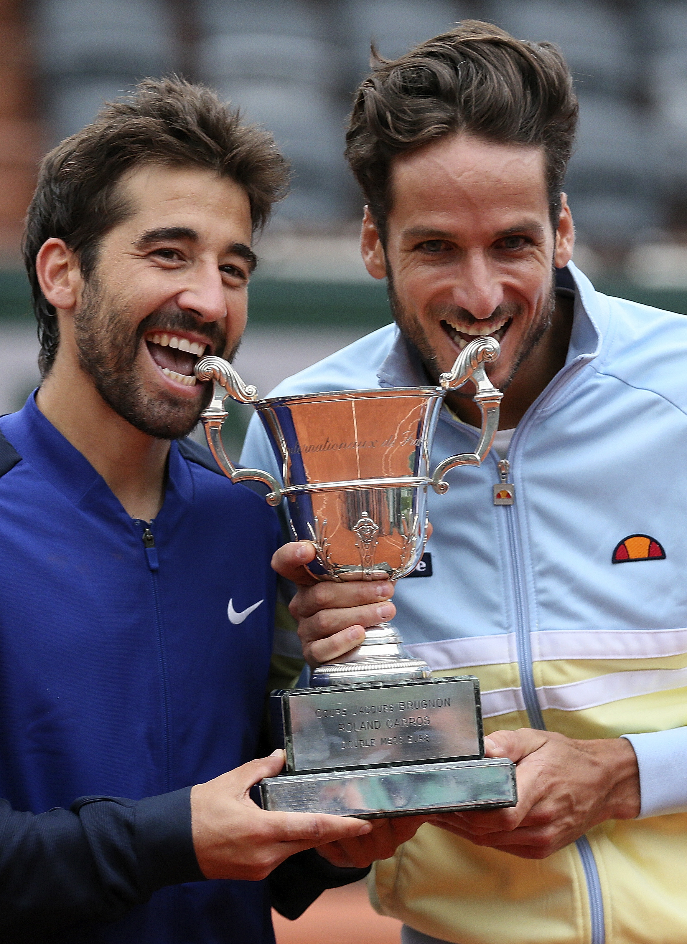Spanish pair Feliciano Lopez, right, and Marc Lopez bite their trophy after winning the men's doubles final match of the French Open tennis tournament against Bob and Mike Bryan, of the U.S,  at the Roland Garros stadium, Saturday, June 4, 2016 in Paris.