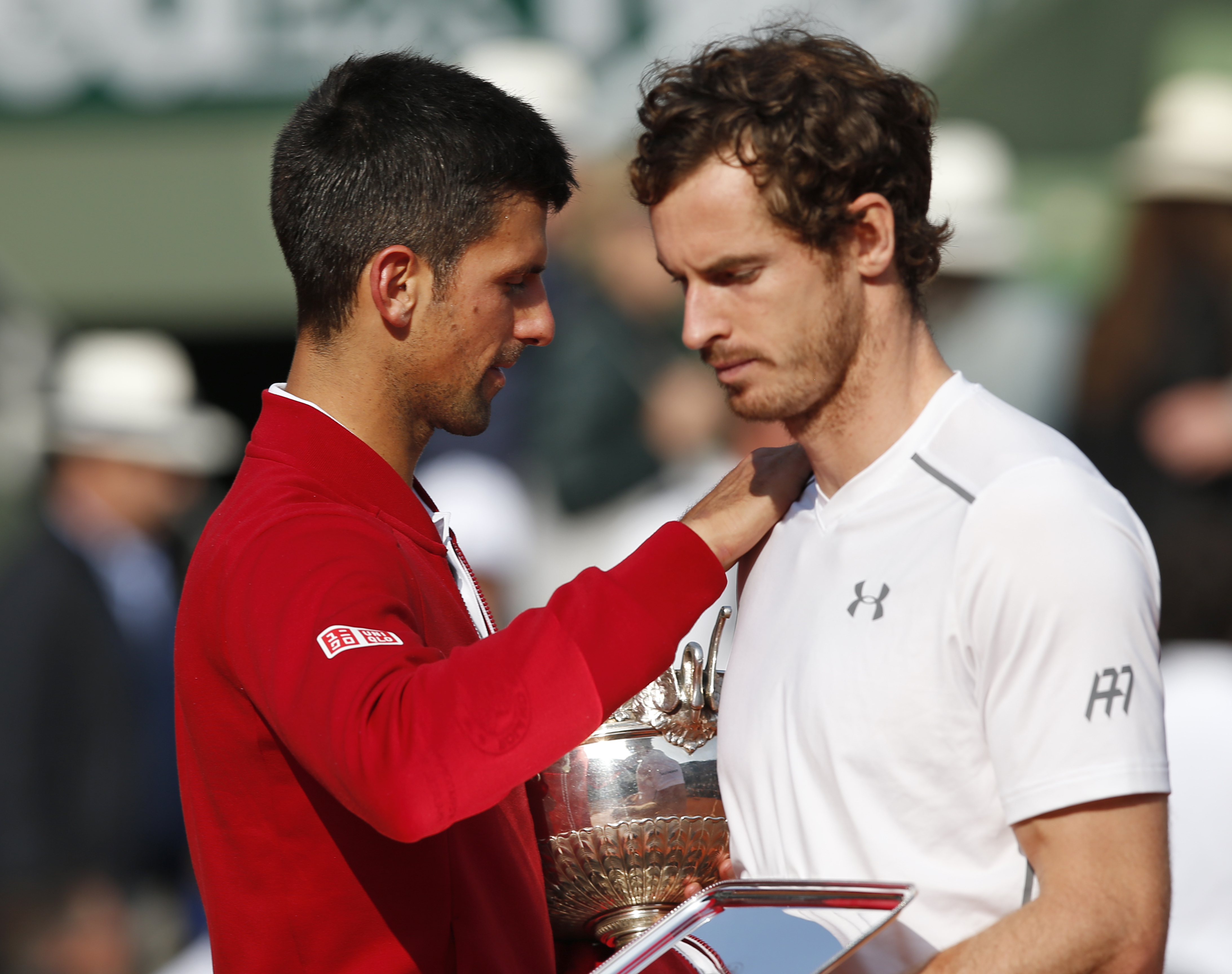 Serbia's Novak Djokovic, left, comforts Britain's Andy Murray who holds the runner-up trophy after losing the final of the French Open tennis tournament against Djokovic in four sets 3-6, 6-1, 6-2, 6-4, at the Roland Garros stadium in Paris, France, Sunda
