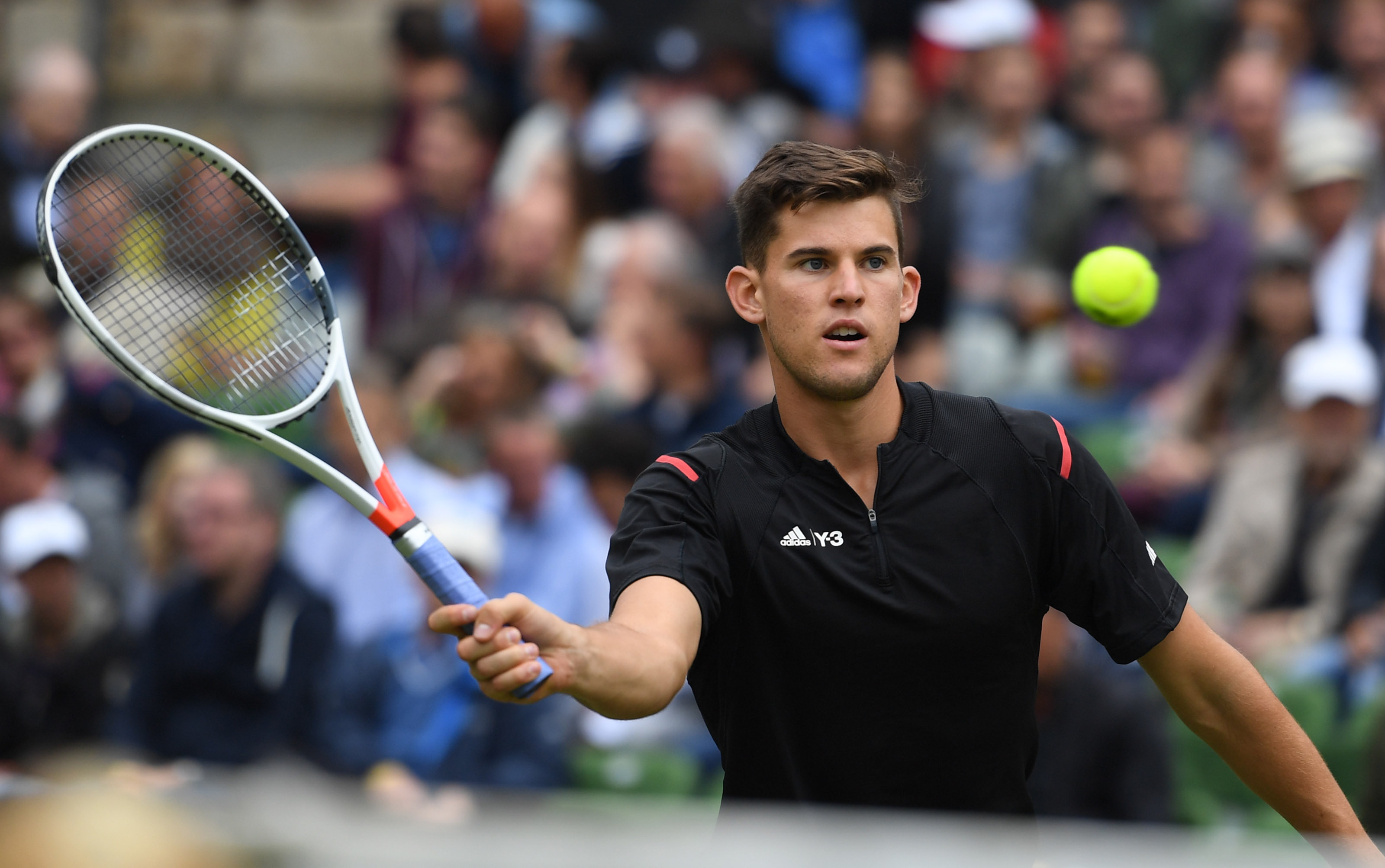 Dominic Thiem from Austria returns a ball to Roger Federer from Switzerland during the semifinals at the MercedesCup  ATP  tennis tournament in Stuttgart, Germany, Saturday June 11,  2016.  (Marijan Murat/dpa via AP)