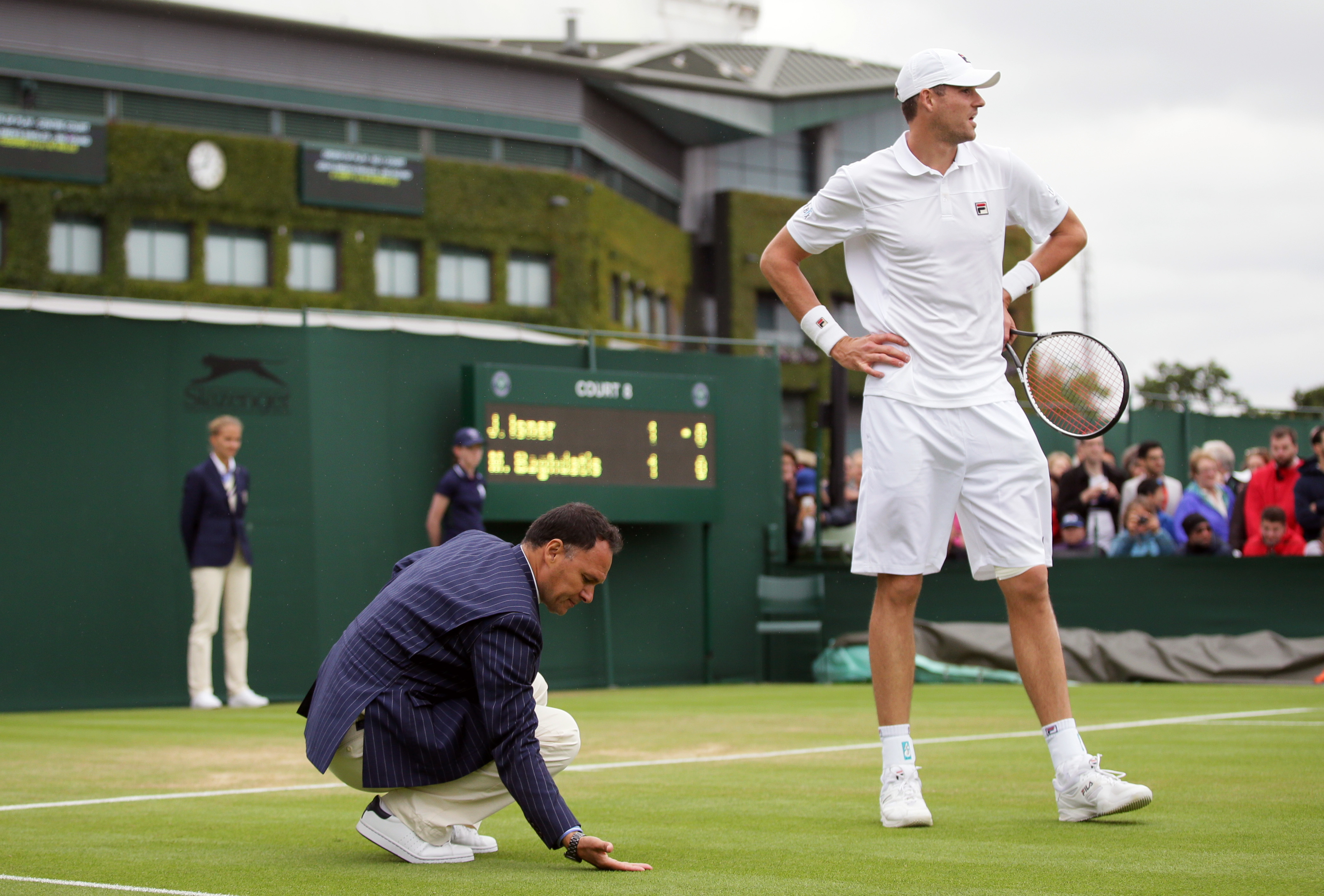 The umpire checks the ground for rain during the men's singles match between John Isner of the US, right, and Marcos Baghdatis of Cyprus on day three of the Wimbledon Tennis Championships in London, Wednesday, June 29, 2016. (AP Photo/Tim Ireland)
