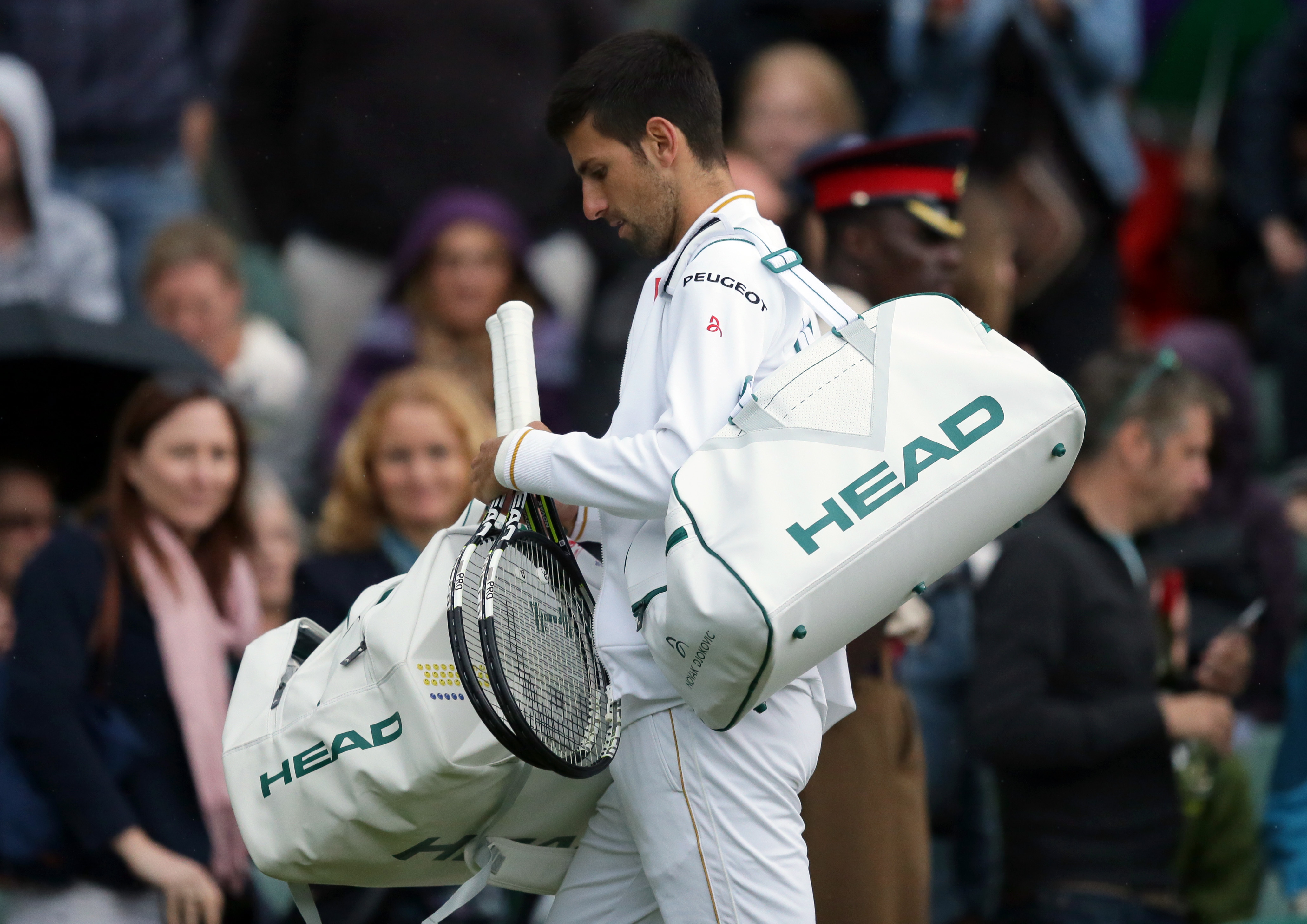 Novak Djokovic of Serbia leaves the court as rain stops his men's singles match against Sam Querrey of the U.S on day five of the Wimbledon Tennis Championships in London, Friday, July 1, 2016. (AP Photo/Tim Ireland)