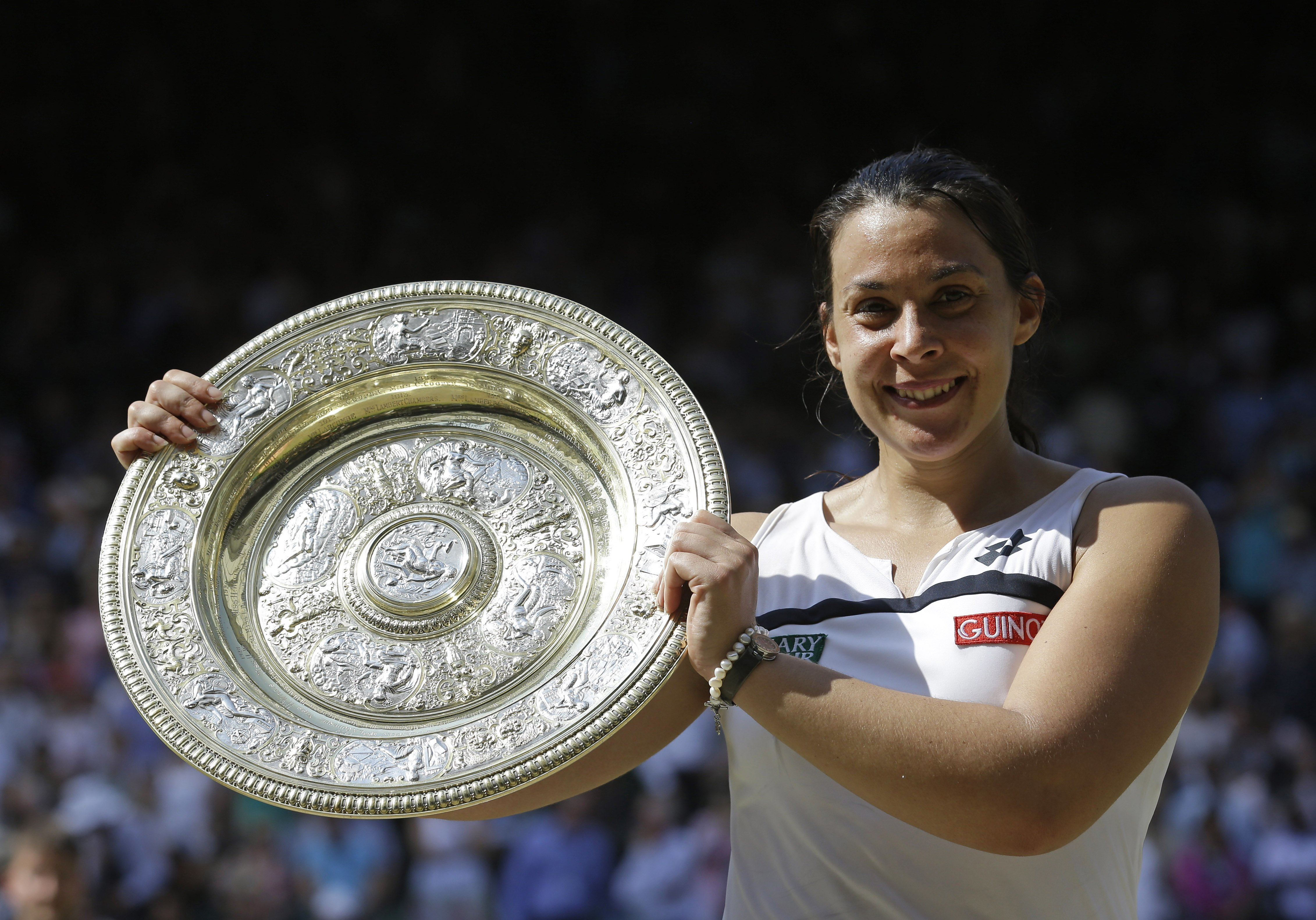 FILE - A  Saturday, July 6, 2013 file photo showing Marion Bartoli of France smiling as she holds the trophy after winning the Women's singles final match against Sabine Lisicki of Germany at the All England Lawn Tennis Championships in Wimbledon, London.