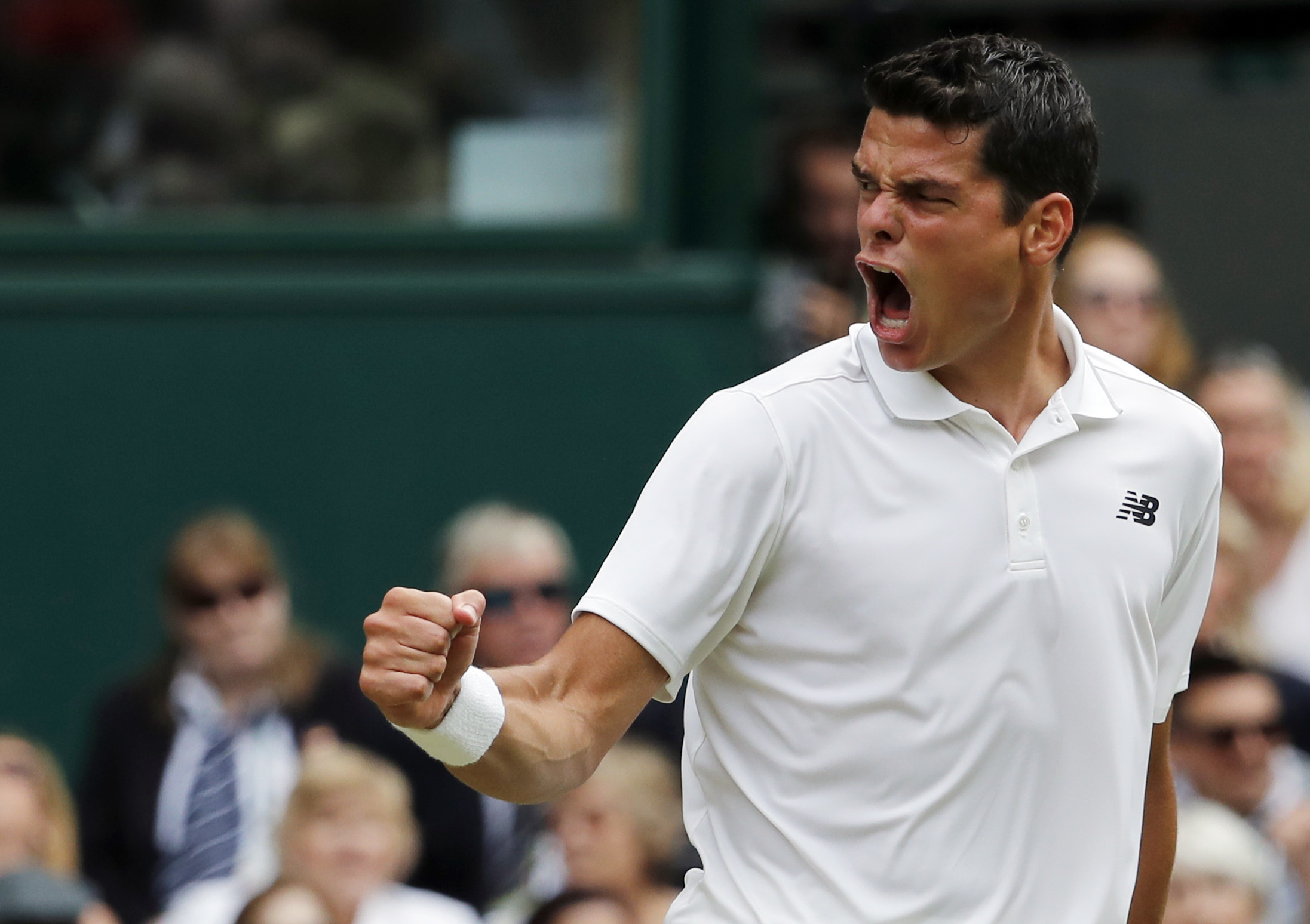 Milos Raonic of Canada celebrates a point against Roger Federer of Switzerland during their men's semifinal singles match on day twelve of the Wimbledon Tennis Championships in London, Friday, July 8, 2016. (AP Photo/Ben Curtis)