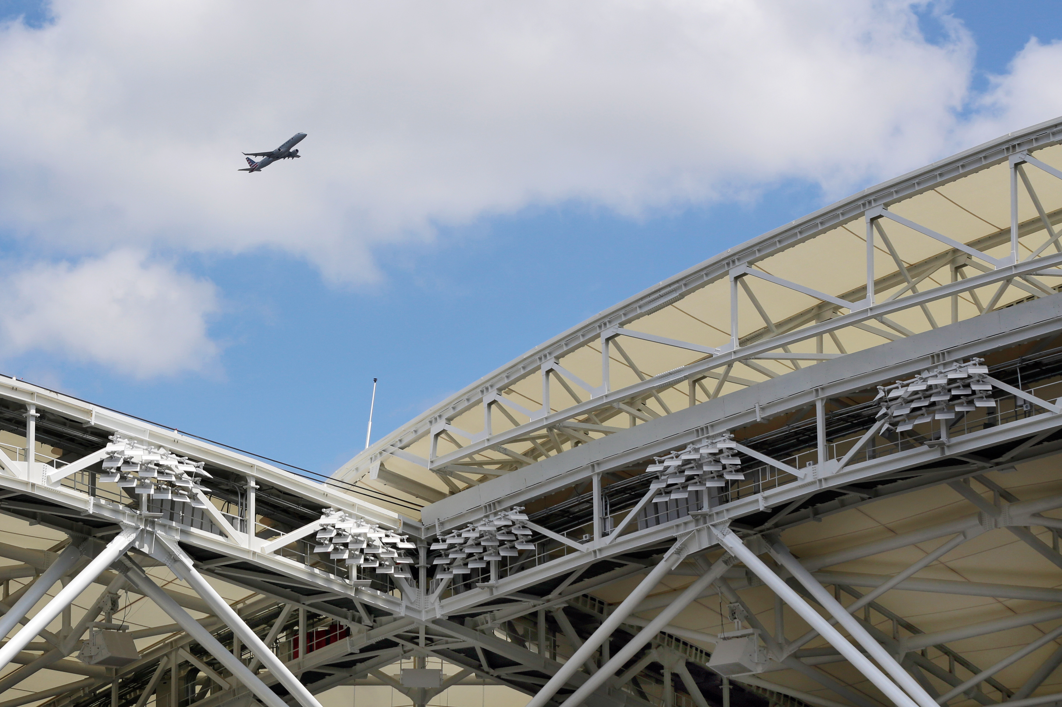 An airplane taking off from LaGuardia Airport is seen through the new retractable roof of Arthur Ashe Stadium, at the Billie Jean King National Tennis Center in the Queens borough of New York, Tuesday, Aug. 2, 2016. Mother Nature will no longer be a probl