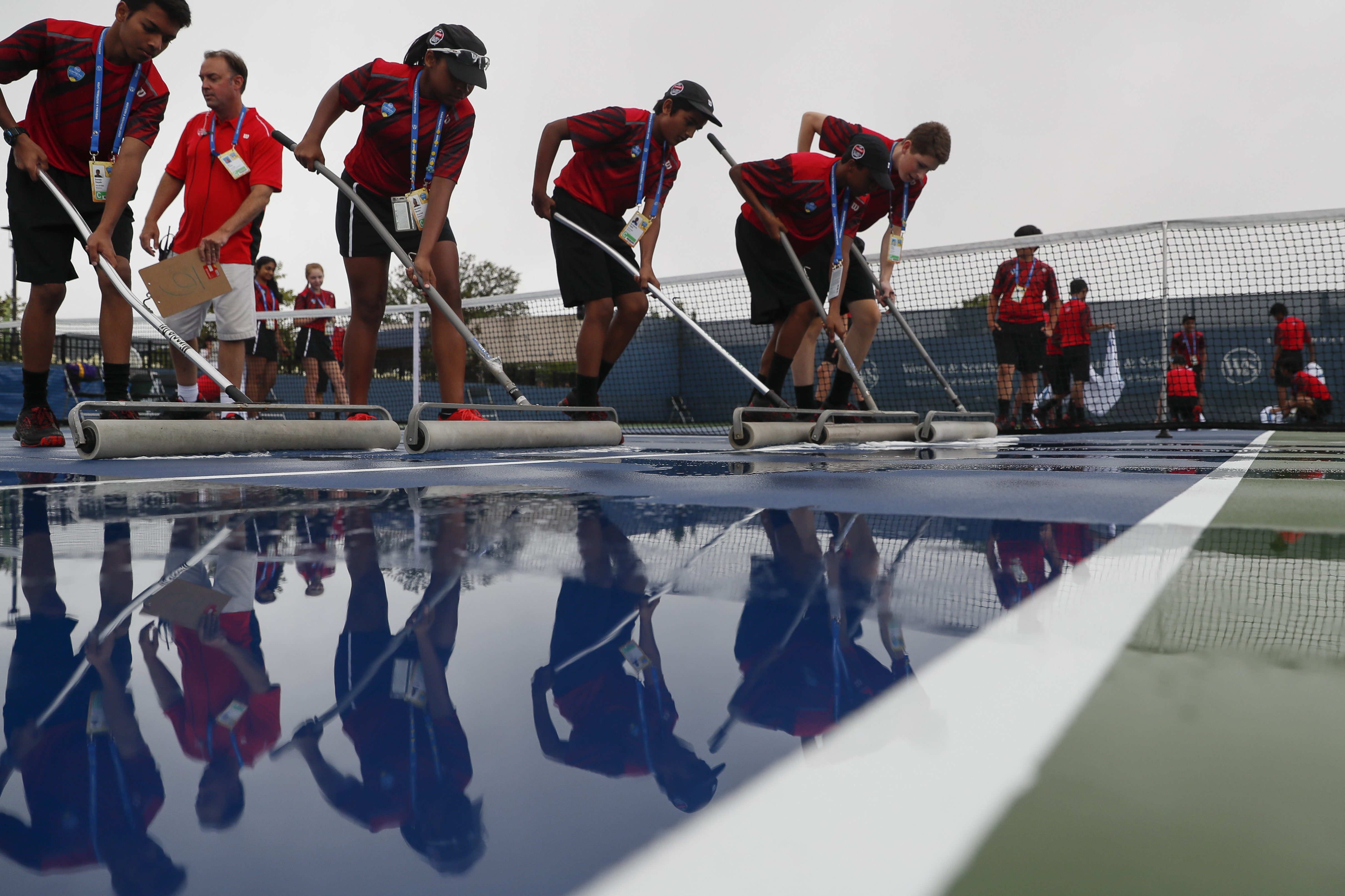 Volunteers prepare the court after rain delayed the opening of the Western & Southern Open tennis tournament, Sunday, Aug. 14, 2016, in Mason, Ohio. (AP Photo/John Minchillo)