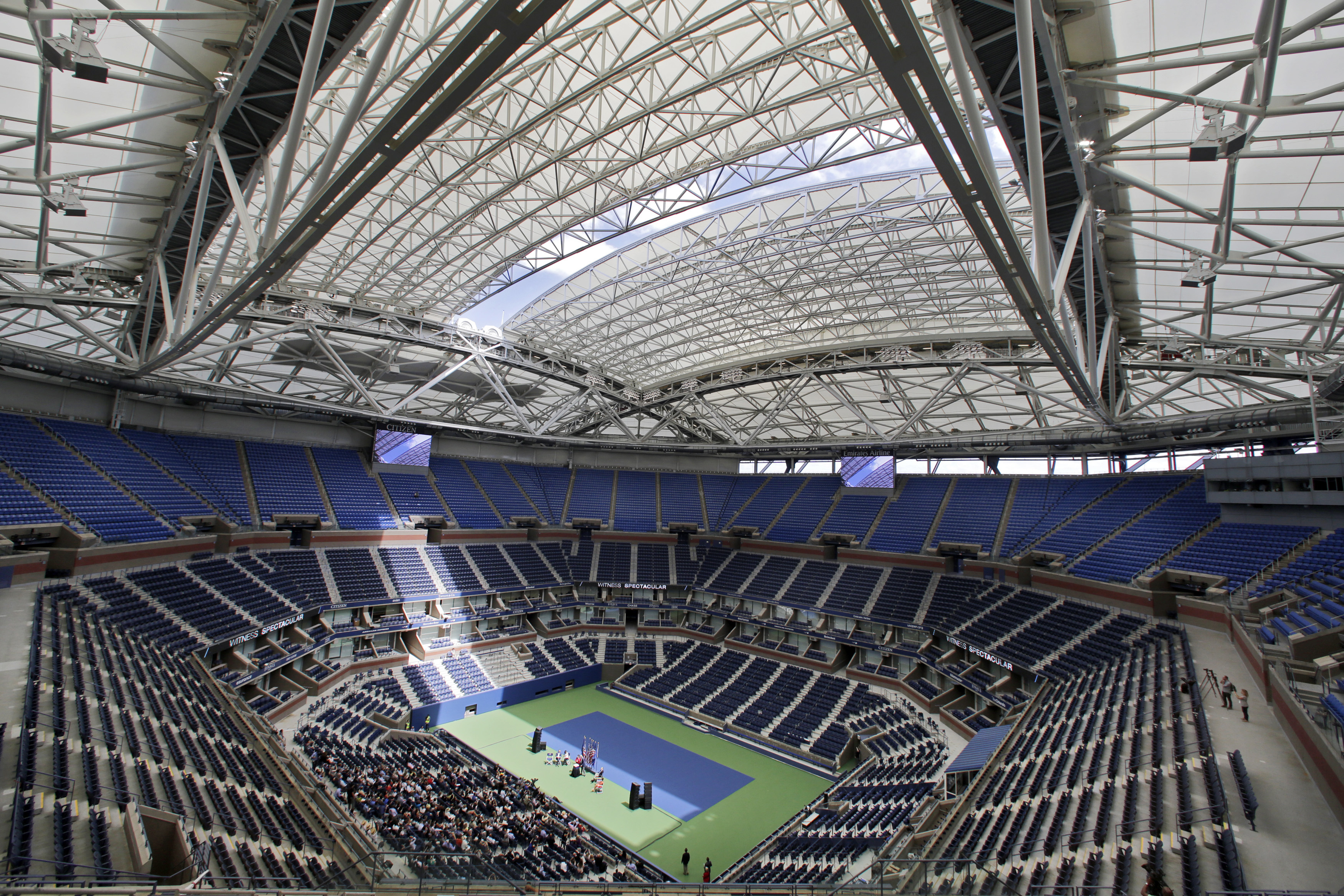 FILE - In this Aug. 2, 2016, file photo, the partially open new retractable roof allows a ribbon of light into Arthur Ashe Stadium at the Billie Jean King National Tennis Center in New York. With the stadium now covered by a retractable roof, players such