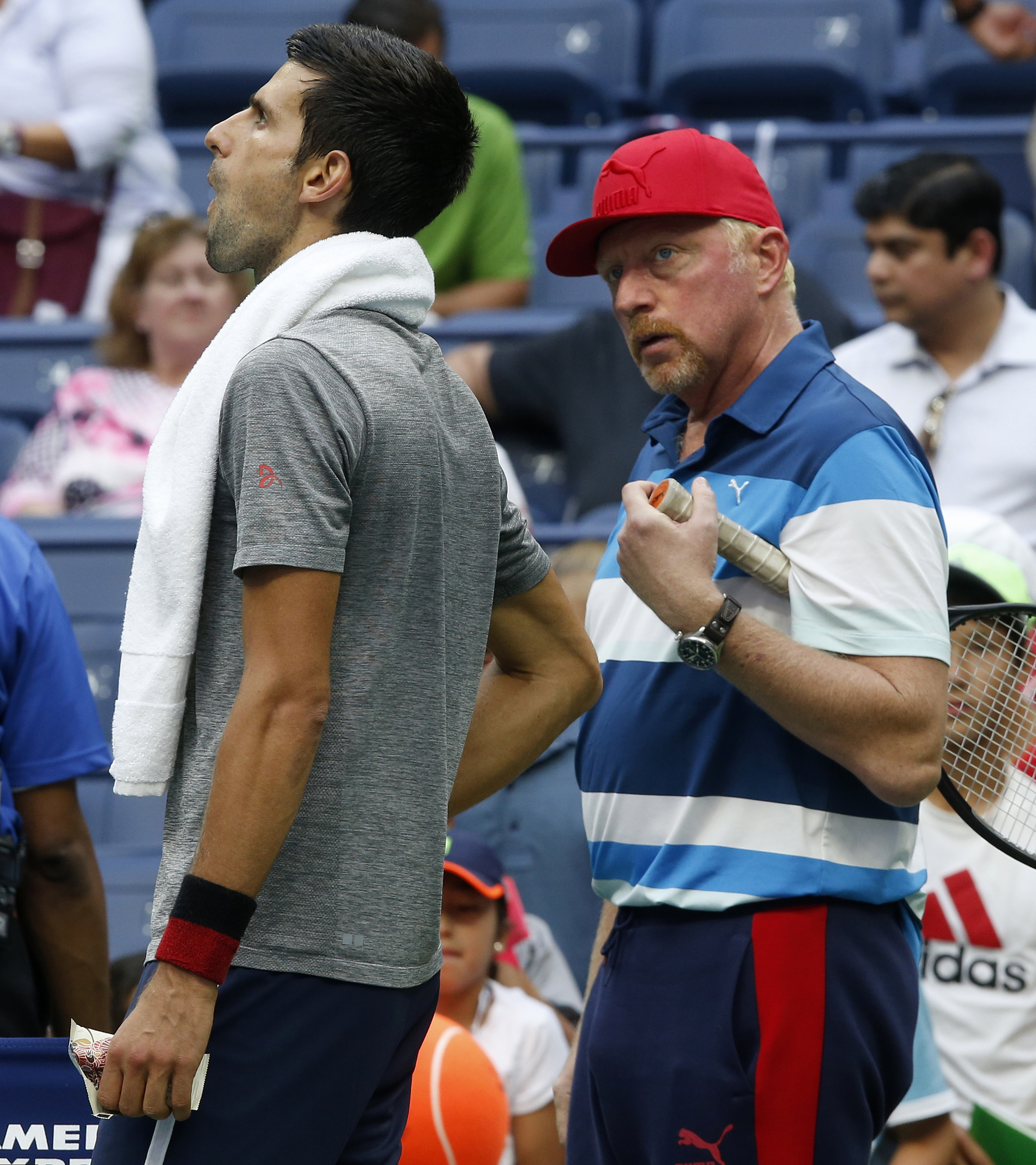 Novak Djokovic, of Serbia, left, talks with his coach Boris Becker, right, during a practice session after his opponent Mikhail Youzhny, of Russia, retired in the first set of their match during the third round of the U.S. Open tennis tournament, Friday,