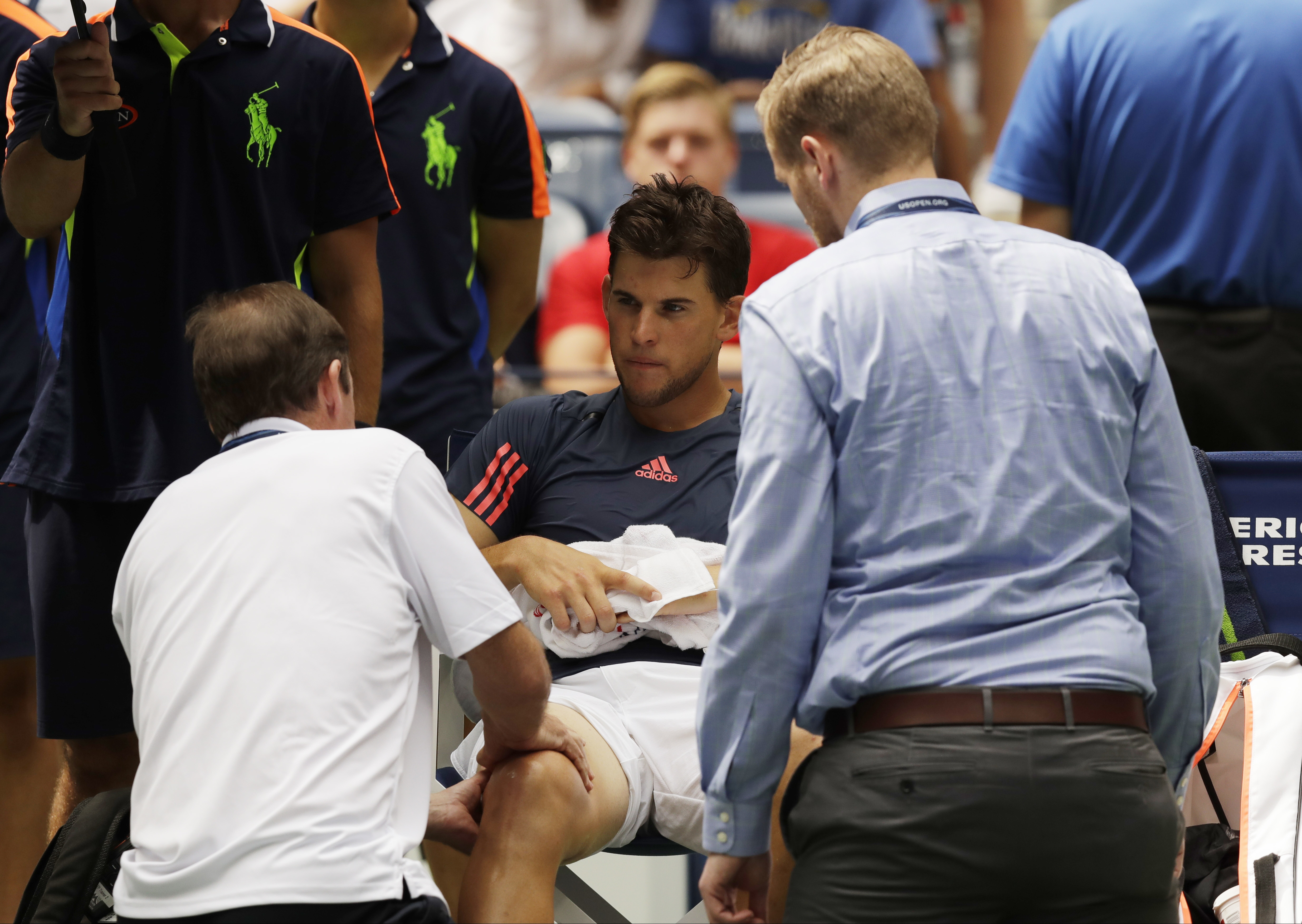 A trainer works on the right leg of Dominic Thiem, of Austria, during the fourth round of the U.S. Open tennis tournament against Juan Martin del Potro, of Argentina, , Monday, Sept. 5, 2016, in New York. (AP Photo/Charles Krupa)