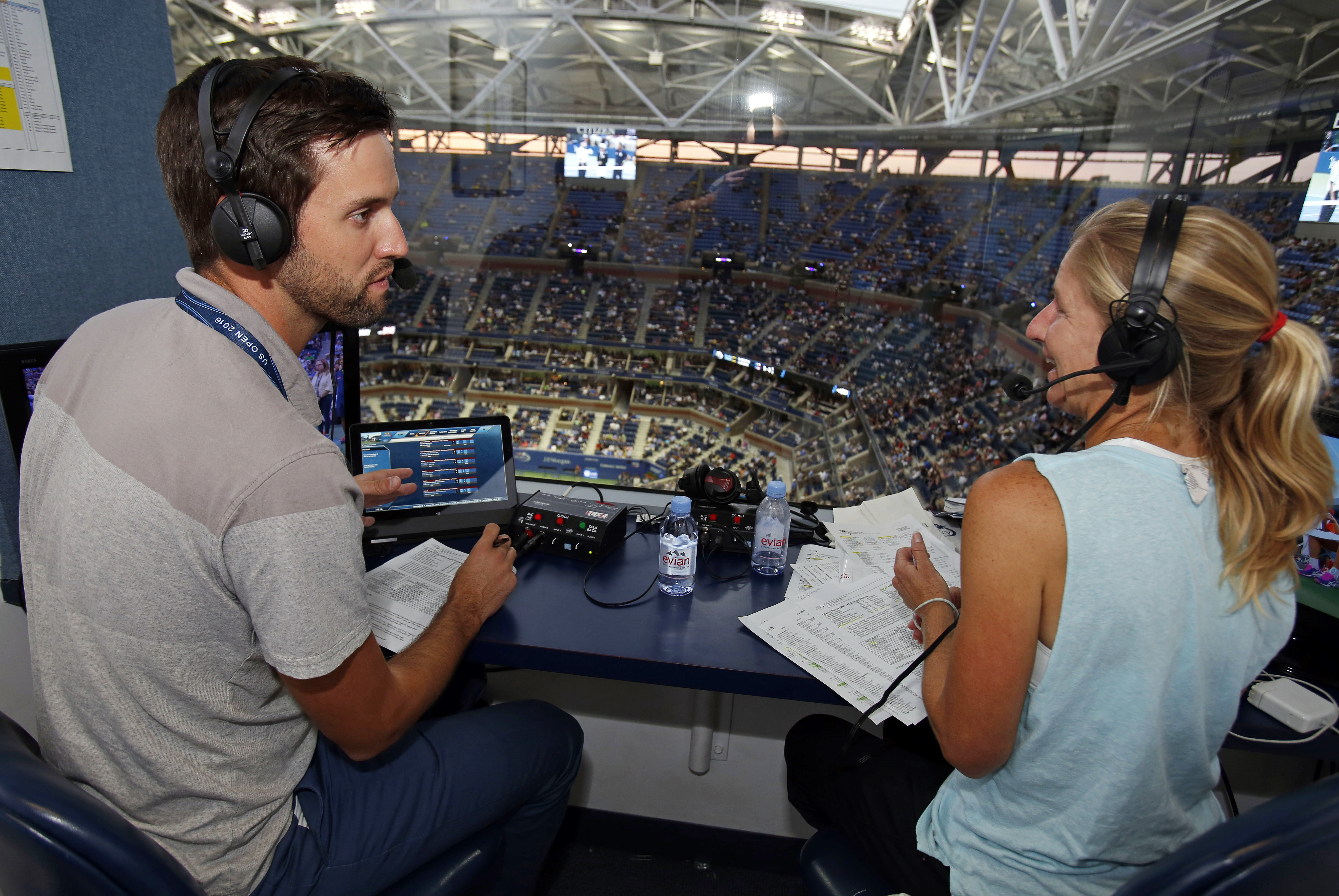 In this Monday, Sept. 5, 2016 photo, U.S. Open Radio broadcasters Brian Clark, left, and Jill Craybas talk during the fourth round of the tennis tournament in New York. Nearly 400 organizations from around the world are covering this year's U.S. Open, yet