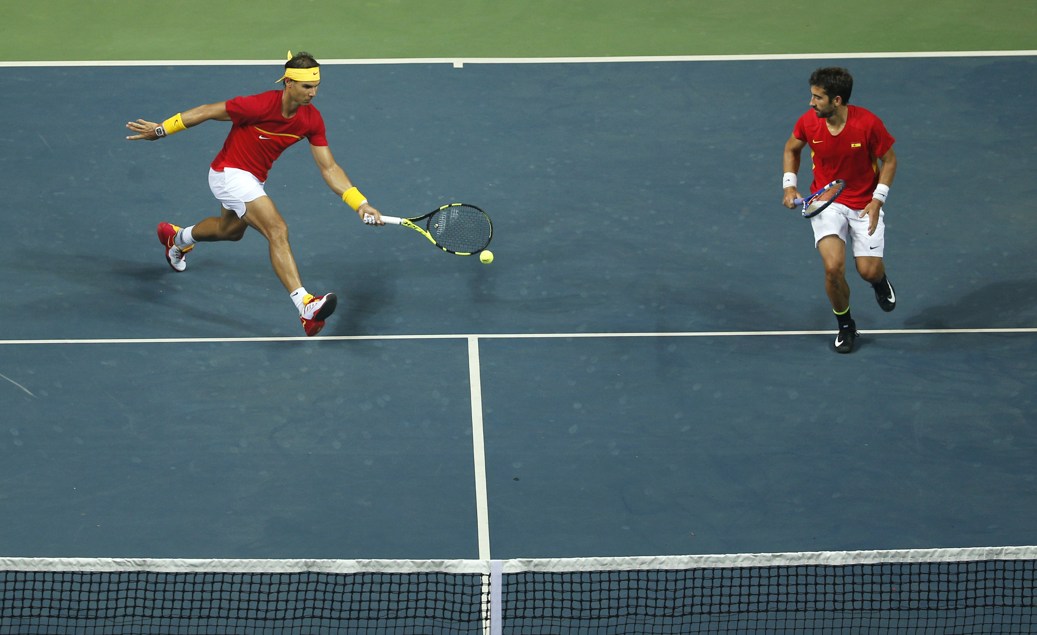 Spain's Rafael Nadal plays a shot, with compatriot Marc Lopez by his side during the Davis Cup world group play-off against India's Leander Paes and Saketh Myneni in New Delhi, India, Saturday, Sept. 17, 2016. (AP Photo/Tsering Topgyal)