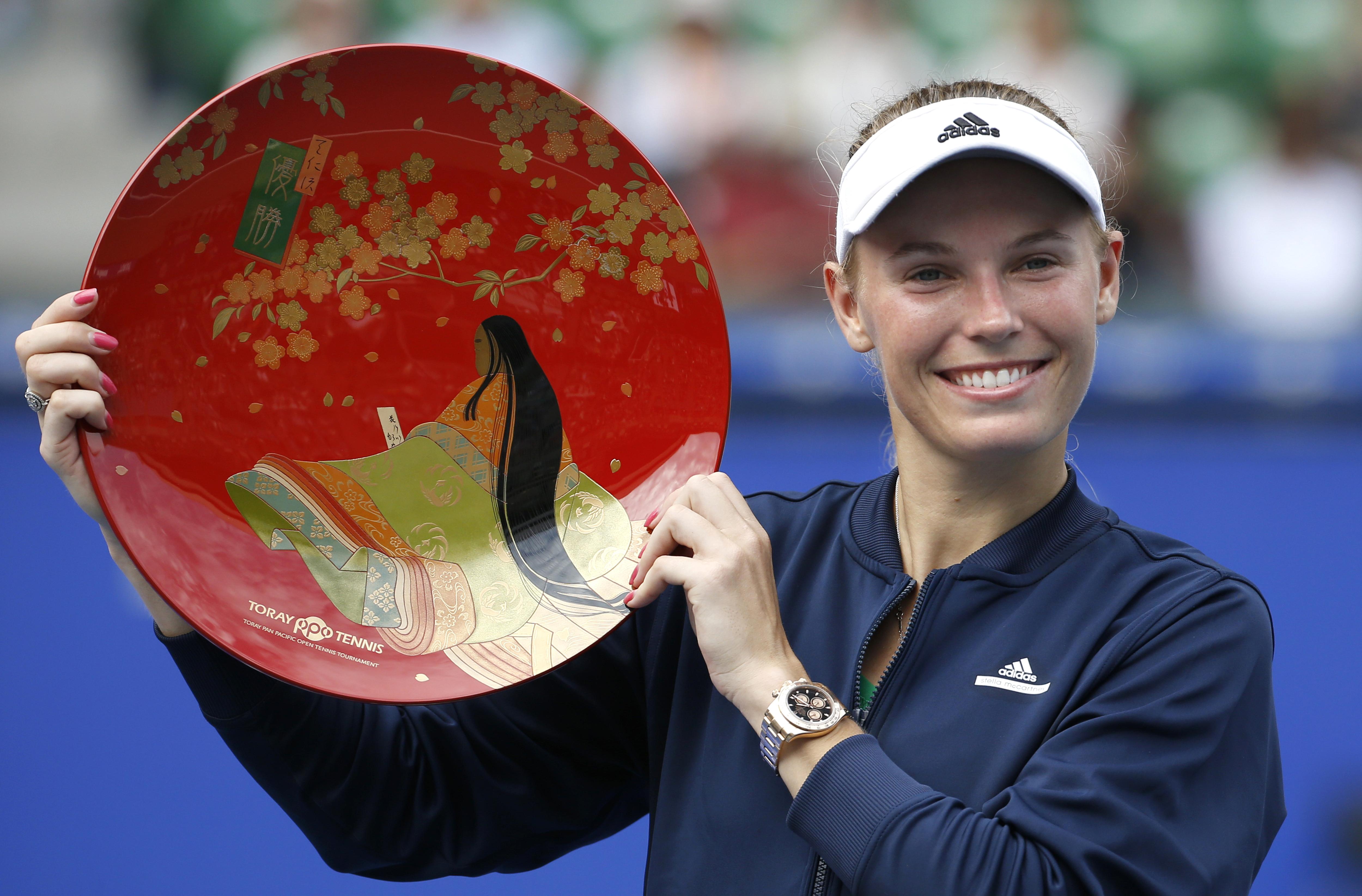 Caroline Wozniacki of Denmark poses with the winner's plate after beating Naomi Osaka of Japan at the Japan Pan Pacific Open tennis tournament in Tokyo, Sunday, Sept. 25, 2016. (AP Photo/Shizuo Kambayashi)