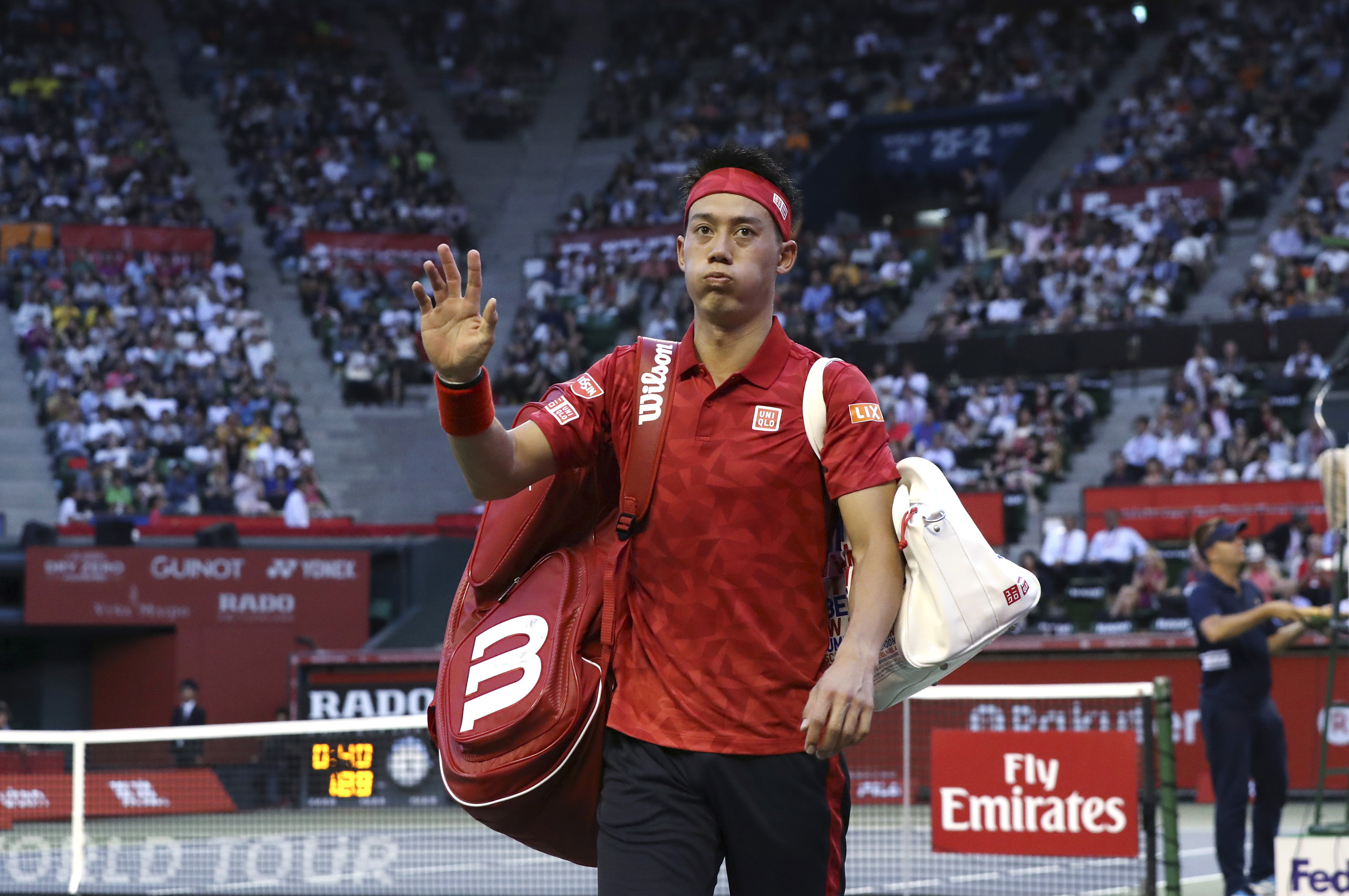Japan's Kei Nishikori walks away from the center court after he retired from his match against Joao Sousa of Portugal during their singles match at the Japan Open mens tennis tournament in Tokyo, Wednesday, Oct. 5, 2016. (AP Photo/Eugene Hoshiko)