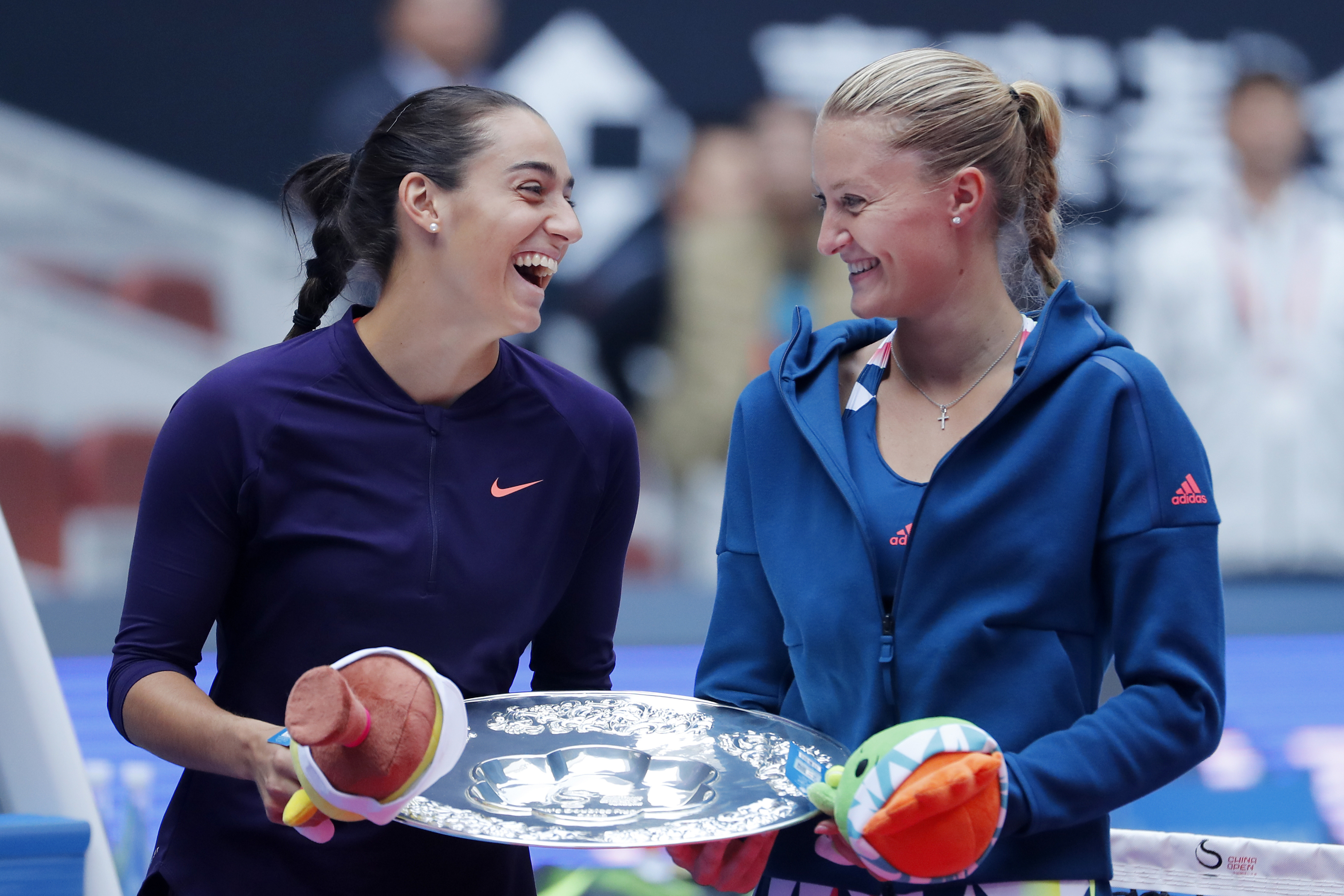 Caroline Garcia, left, and Kristina Mladenovic of France sharing a light moment with their trophy after losing to Lucie Safarova of the Czech Republic, left, and Bethanie Mattek-Sands of the United States in the women's doubles final match of the China Op