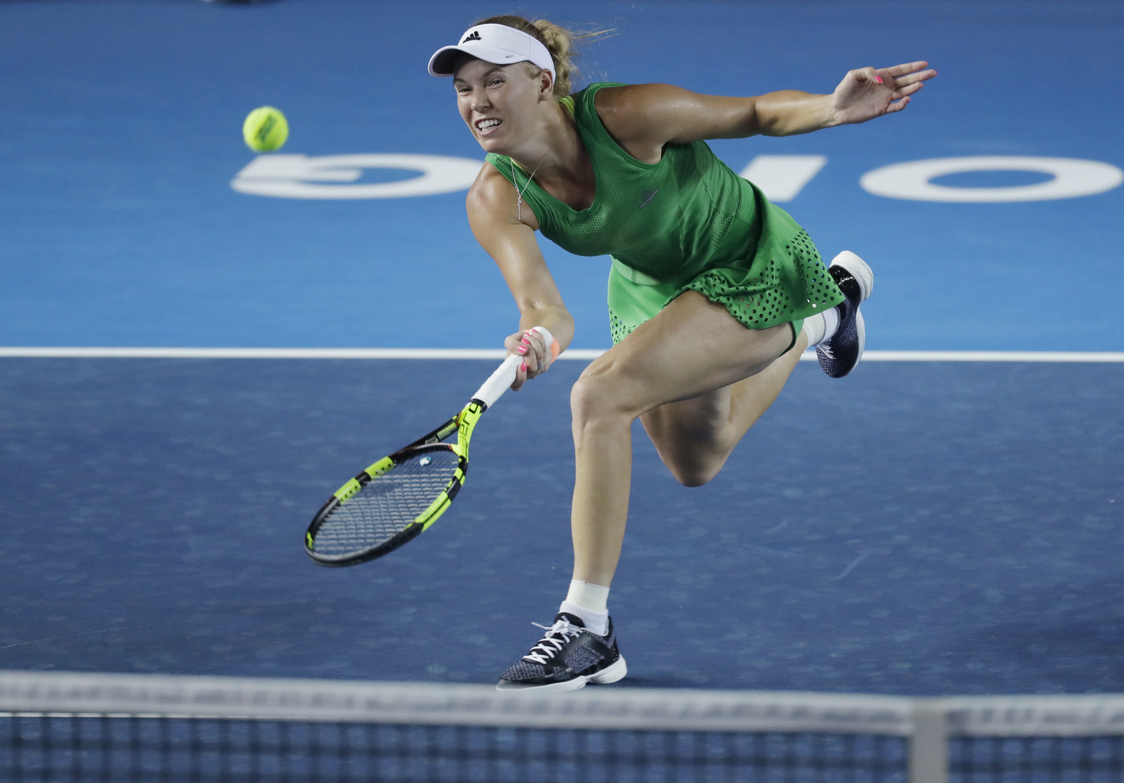 Caroline Wozniacki of Denmark returns a shot to Jelena Jankovic of Serbia during the semi-final match at the Hong Kong Open tennis tournament in Hong Kong, Saturday, Oct. 15, 2016. (AP Photo/Kin Cheung)