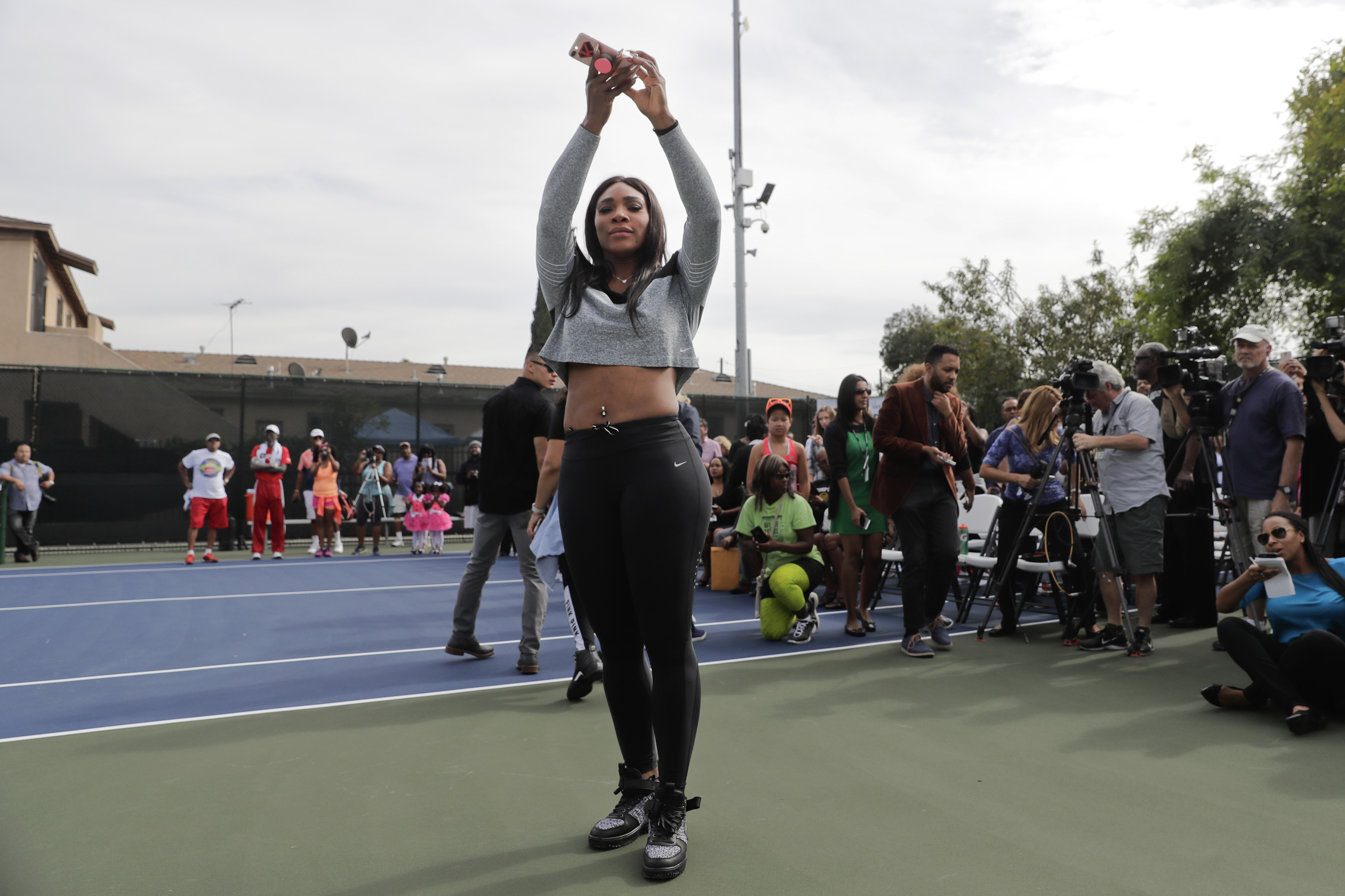 Serena Williams takes pictures of the Leuders Park tennis courts before the start of a dedication ceremony Saturday, Nov. 12, 2016, in Compton, Calif. The Williams sisters were honored with having the courts dedicated in their name. (AP Photo/Jae C. Hong)
