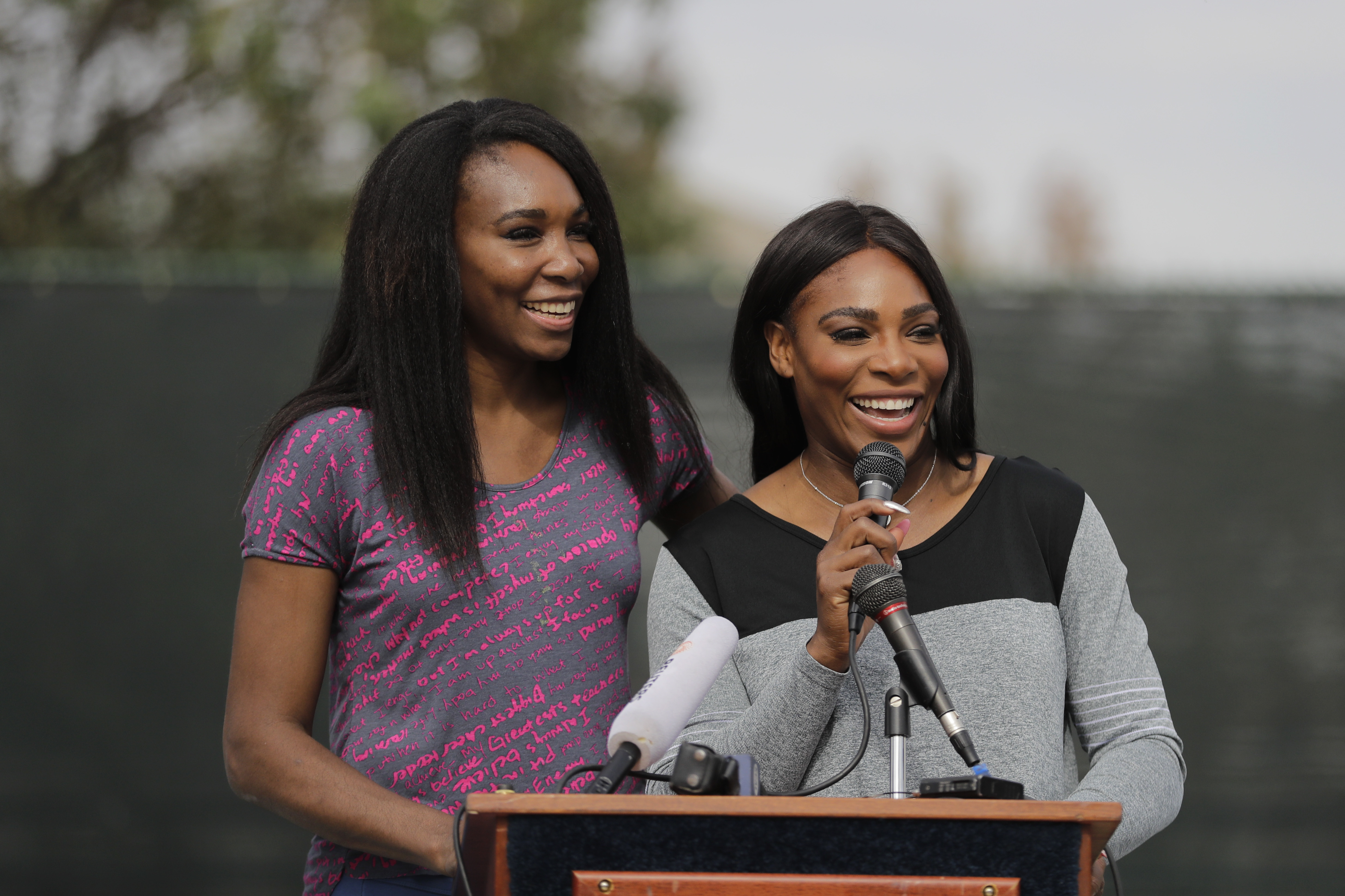 CORRECTS PARK SPELLING TO LUEDERS, NOT LEUDERS - Sister Venus and Serena Williams, right, speak during a dedication ceremony of the Lueders Park tennis courts Saturday, Nov. 12, 2016, in Compton, Calif. The courts were dedicated in their name. (AP Photo/J