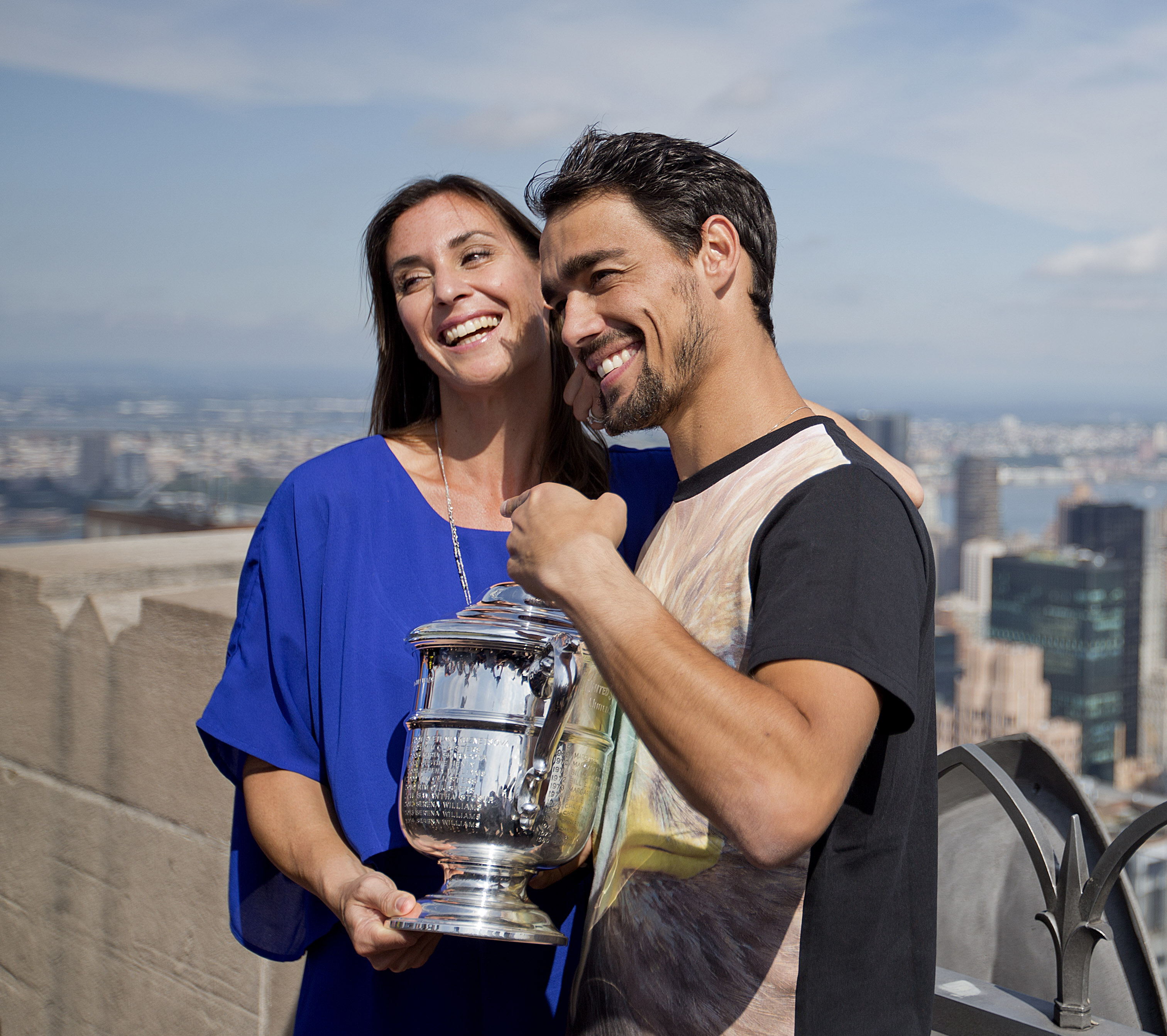 FILe - In this Sept. 13, 2015, file photo, Flavia Pennetta, of Italy, left, poses with her then-fiance and fellow tennis player Fabio Fognini with the U.S. Open tennis women's singles championship trophy during a visit to the Top of the Rock Observation D