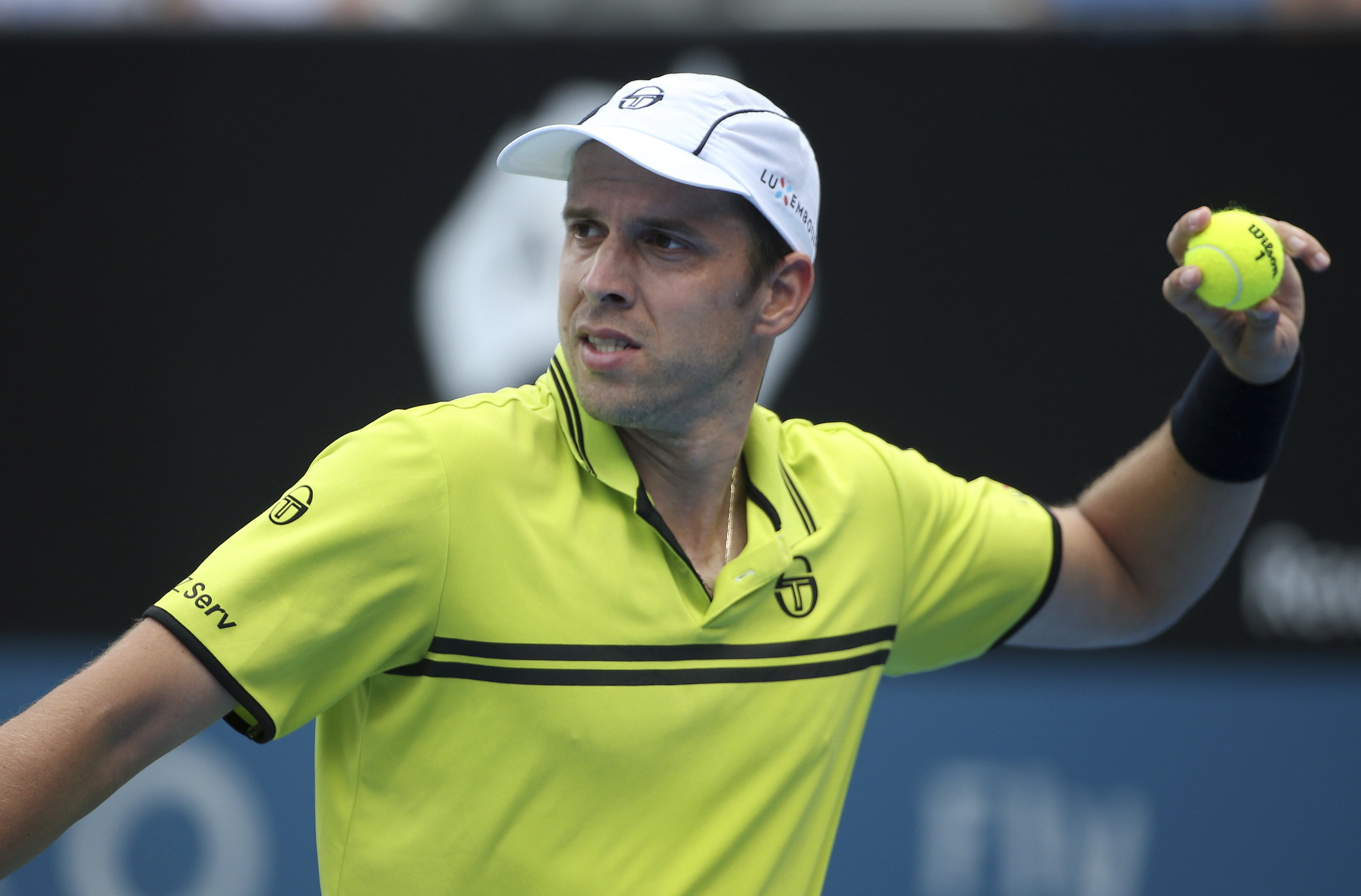 Gilles Muller of Luxembourg throws a ball while playing Pablo Cuevas of Uruguay during their men's quarterfinal singles match at the Sydney International tennis tournament in Sydney Thursday, Jan. 12, 2017. (AP Photo/Rick Rycroft)