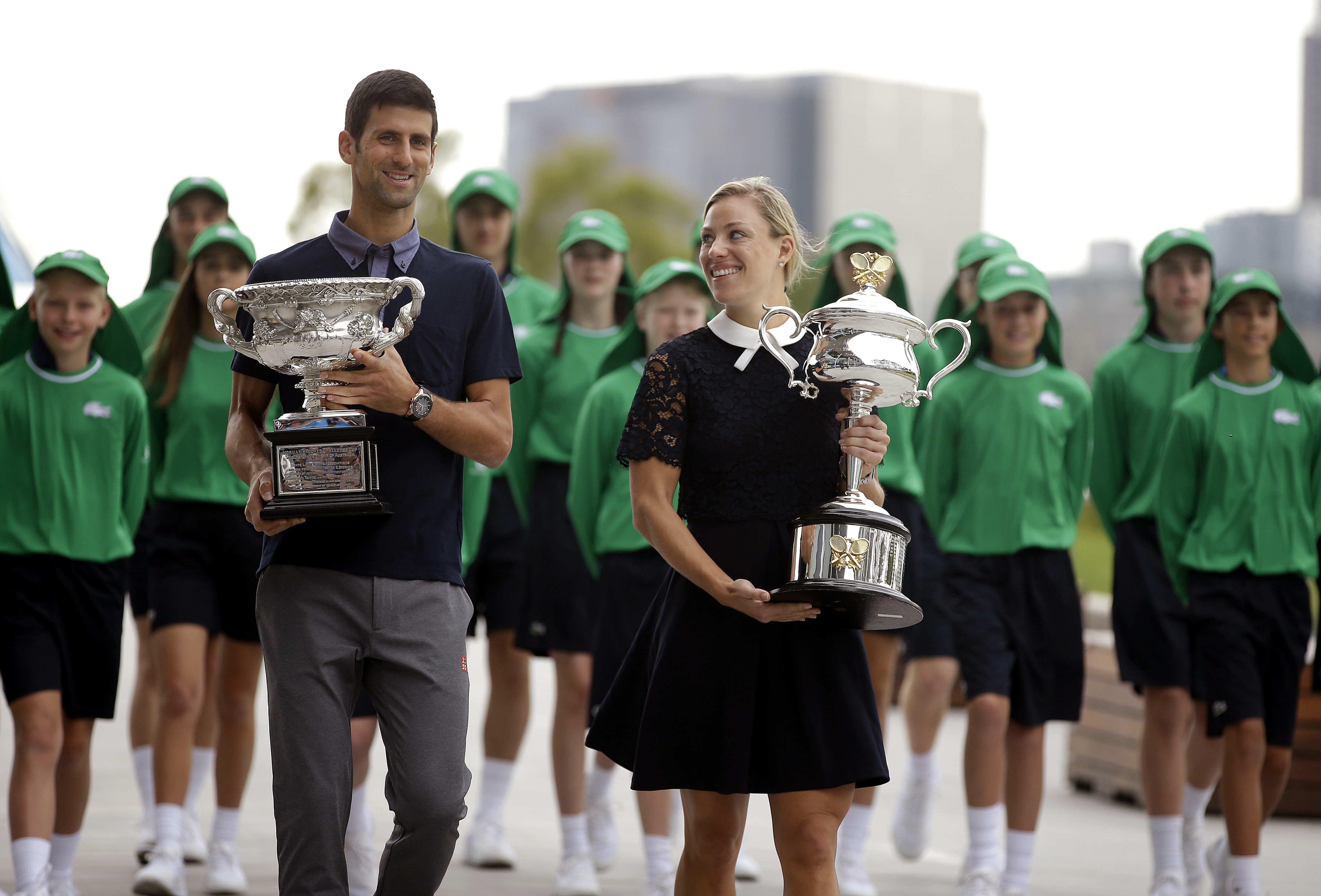 Defending men's and woman's champions Serbia's Novak Djokovic, left, and Germany's Angelique Kerber carry their trophies to the official draw ceremony ahead of the Australian Open tennis championships in Melbourne, Australia, Friday, Jan. 13, 2017. (AP Ph