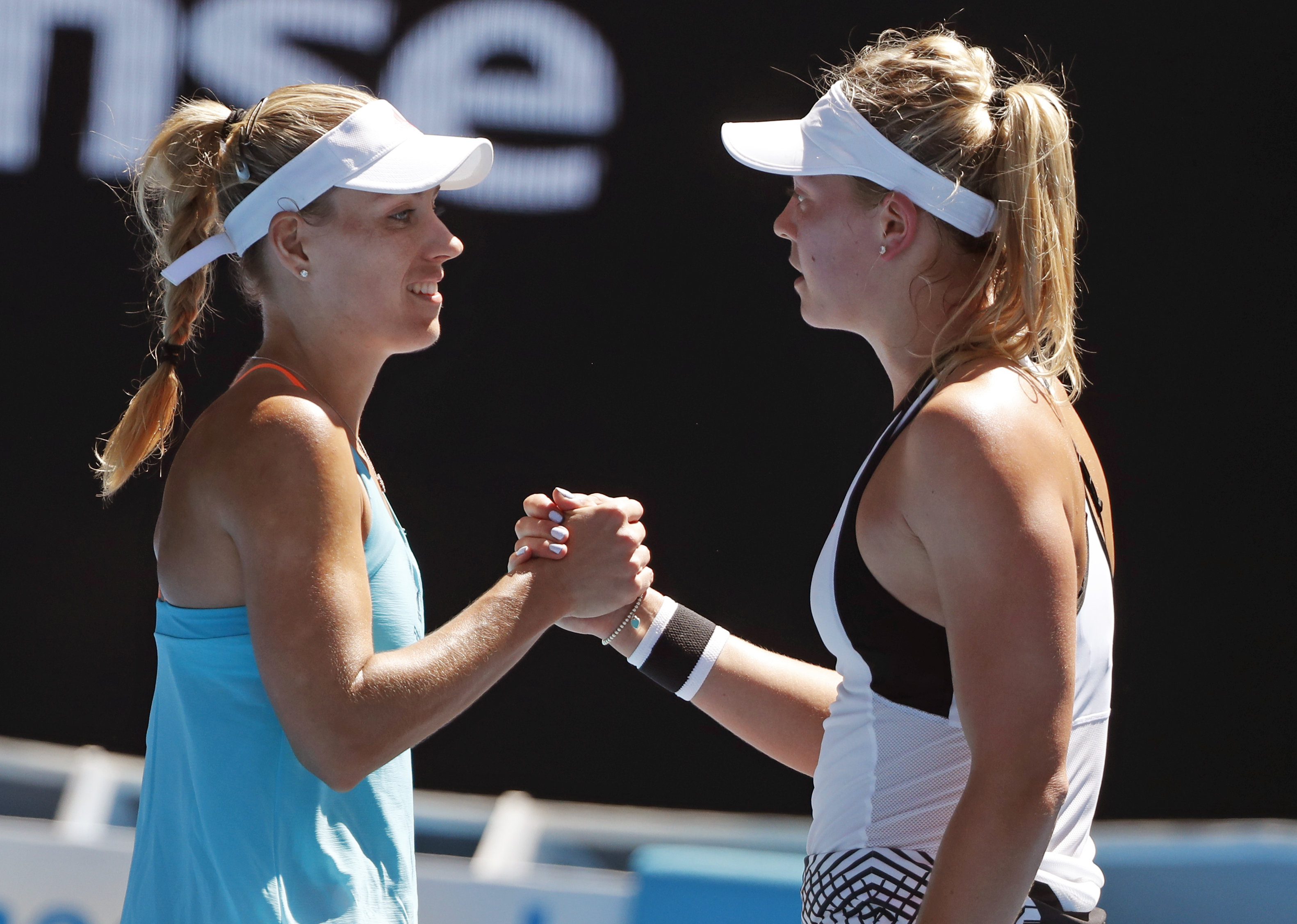 Germany's Angelique Kerber, left, is congratulated by compatriot Carina Witthoeft after wining their second round match at the Australian Open tennis championships in Melbourne, Australia, Wednesday, Jan. 18, 2017. (AP Photo/Dita Alangkara)