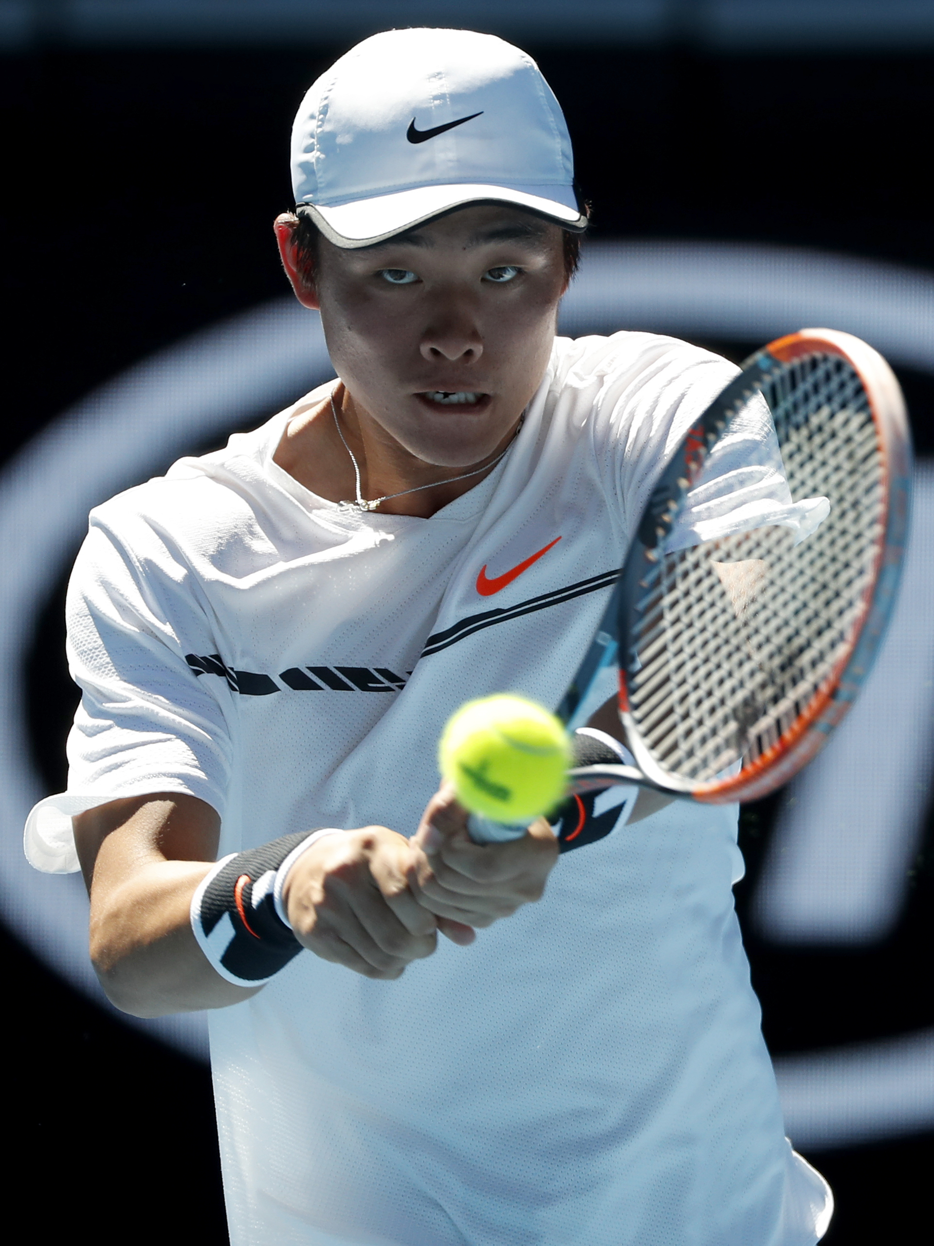 China's Wu Yibing plays a backhand return to Israel's Yshai Oliel during their junior boys' singles semifinal at the Australian Open tennis championships in Melbourne, Australia, Friday, Jan. 27, 2017. (AP Photo/Dita Alangkara)