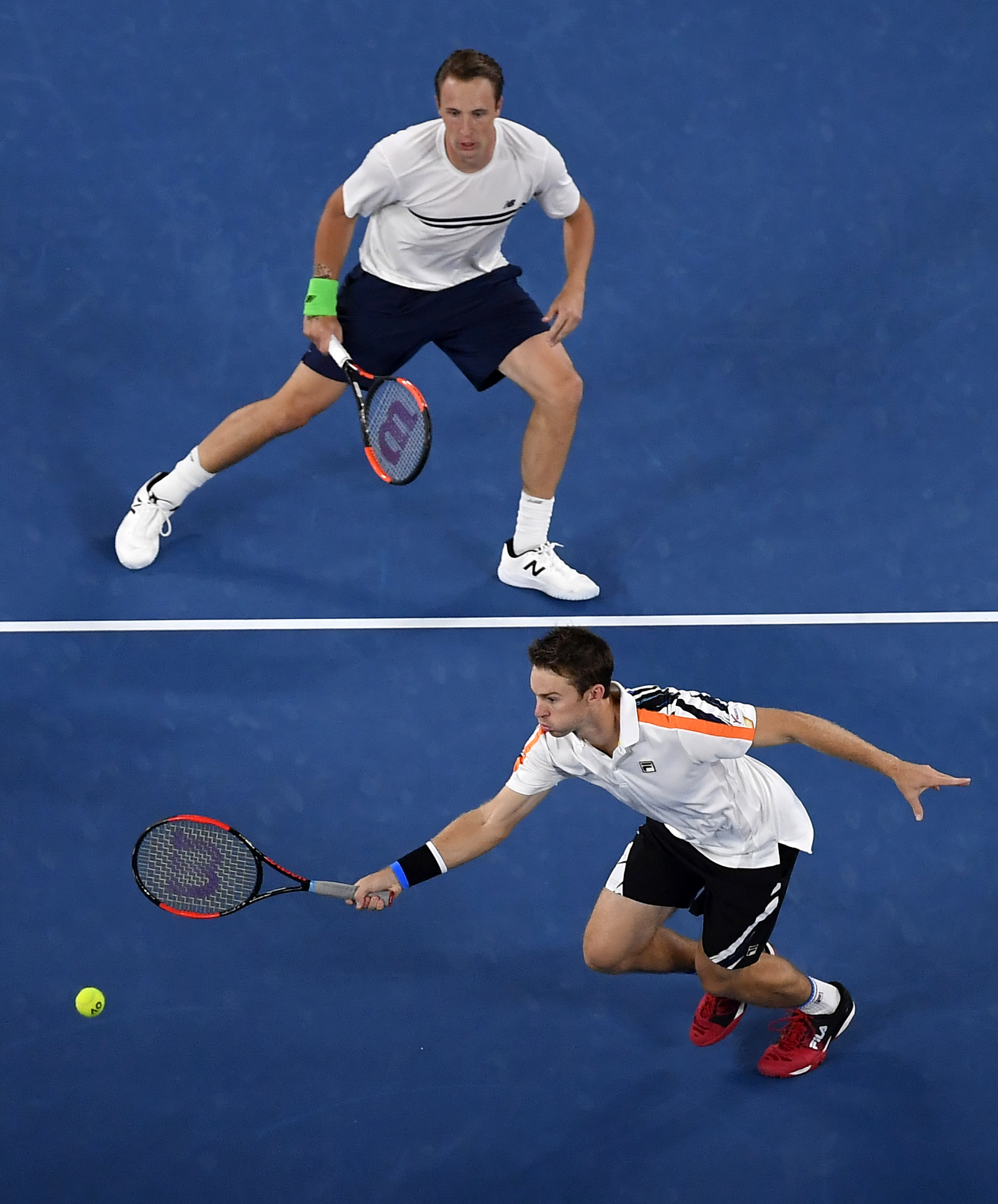 Finland's Henri Kontinen, top, watches his partner Australia's John Peers hits a forehand return in the men's doubles final against Bob and Mike Bryan of the U.S. at the Australian Open tennis championships in Melbourne, Australia, Saturday, Jan. 28, 2017