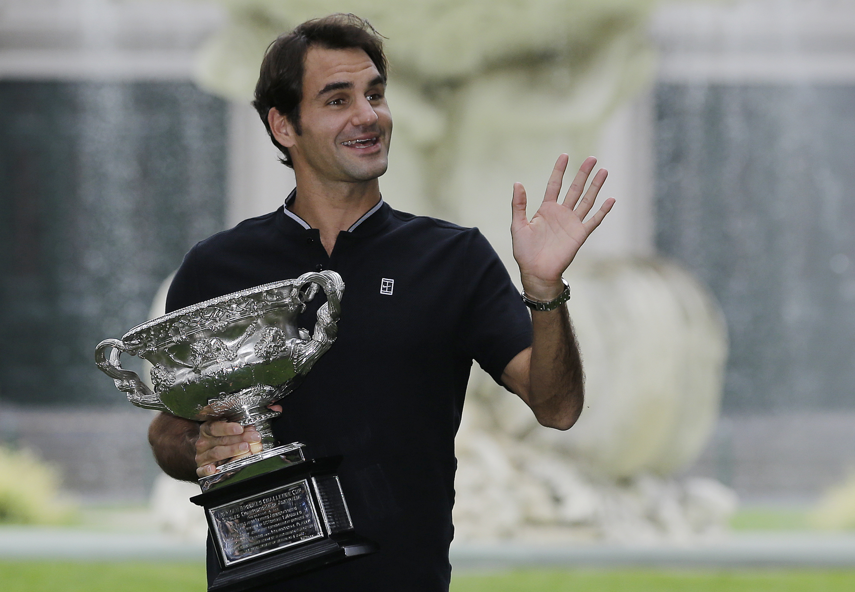 Switzerland's Roger Federer waves to fans as he holds his Australian Open trophy at Carlton Gardens in Melbourne, Australia, Monday, Jan. 30, 2017. Federer defeated Spain's Rafael Nadal in the men's final at the Australian Open tennis championships on Sun