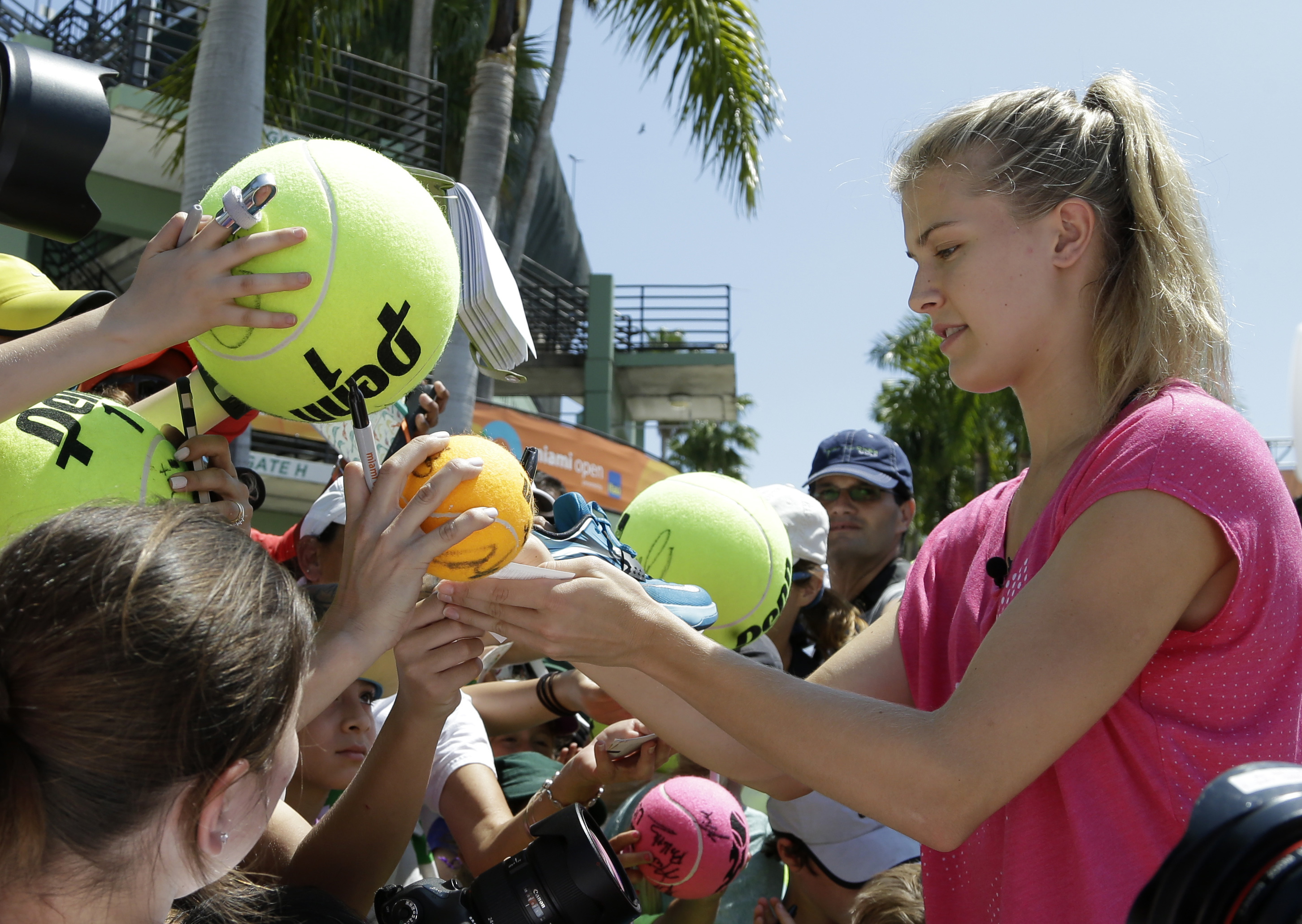 FILE - In this March 24, 2015, file photo, Genie Bouchard, of Canada, signs autographs at the Miami Open tennis tournament in Key Biscayne, Fla. Bouchard may have to go on a date with a fan in order to make good on a Twitter bet made during the Super Bowl