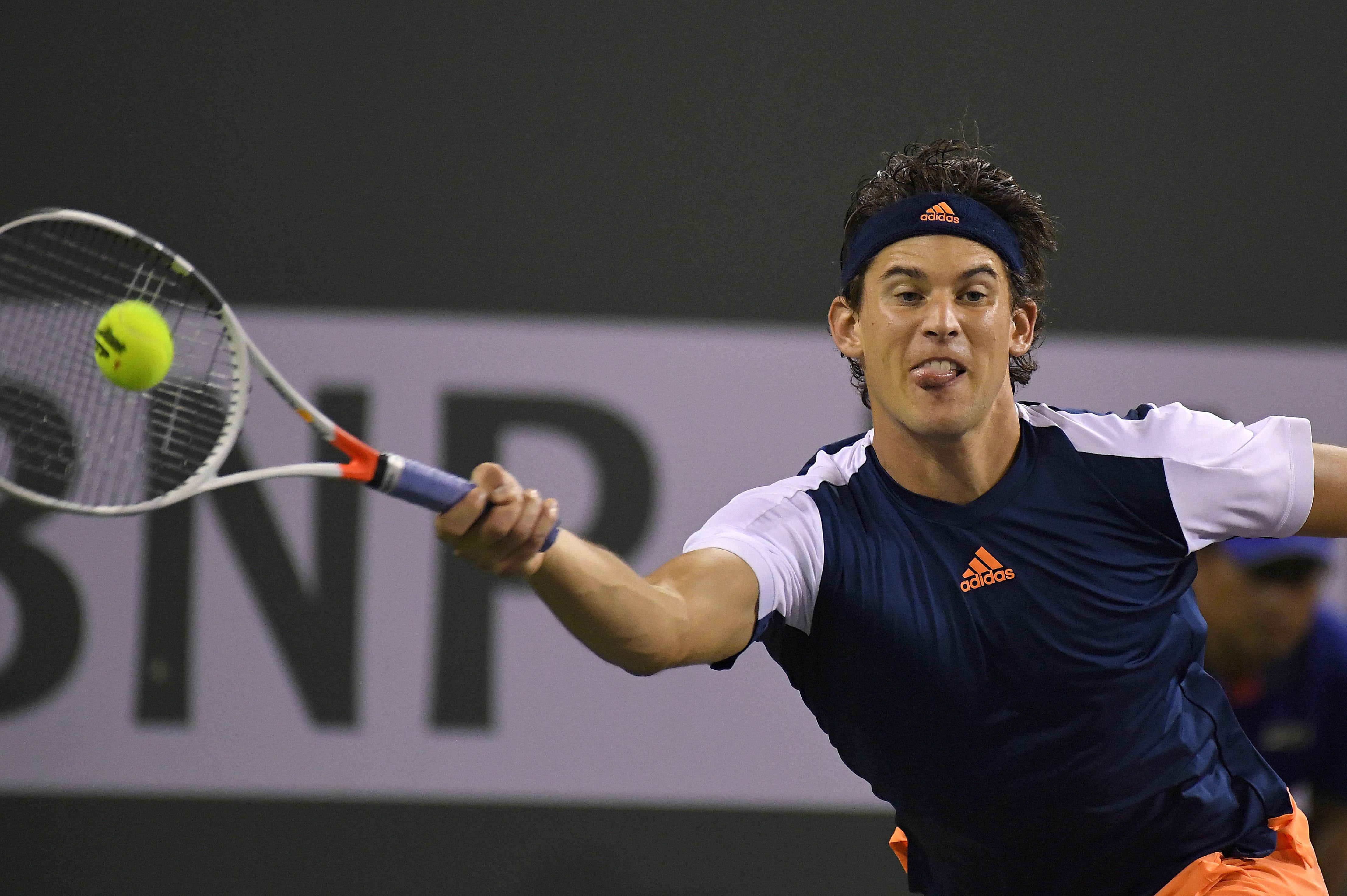 Dominic Thiem, of Austria, returns a shot to Stanislas Wawrinka, of Switzerland, at the BNP Paribas Open tennis tournament, Thursday, March 16, 2017, in Indian Wells, Calif. (AP Photo/Mark J. Terrill)