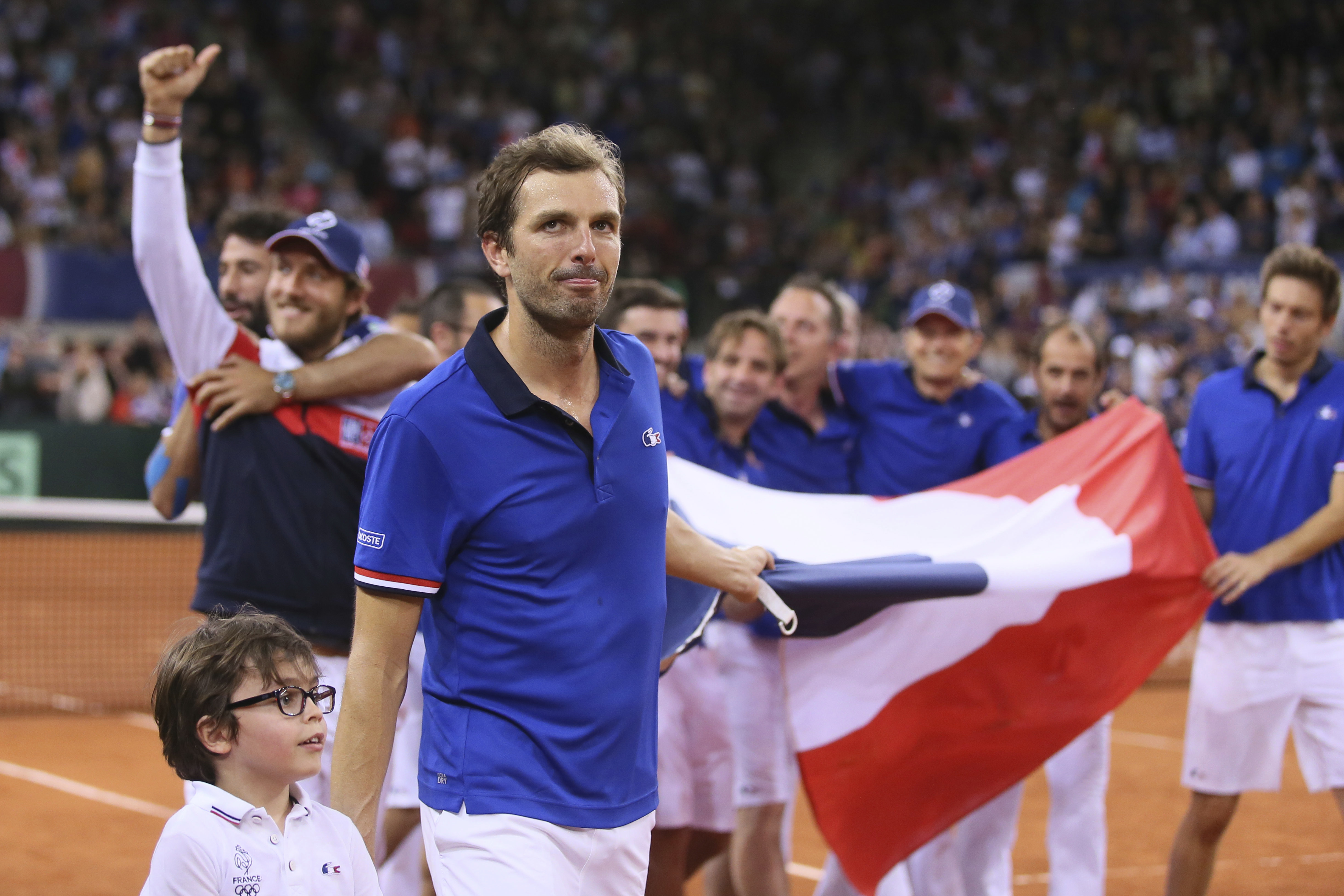 Julien Benneteau of France celebrate with teammate after defeating Jamie Murray and Dominic Inglot of Britain during their doubles Davis Cup quarterfinal tennis match between France and Britain at the Kindarena Stadium of Rouen, France, Saturday, April 8,