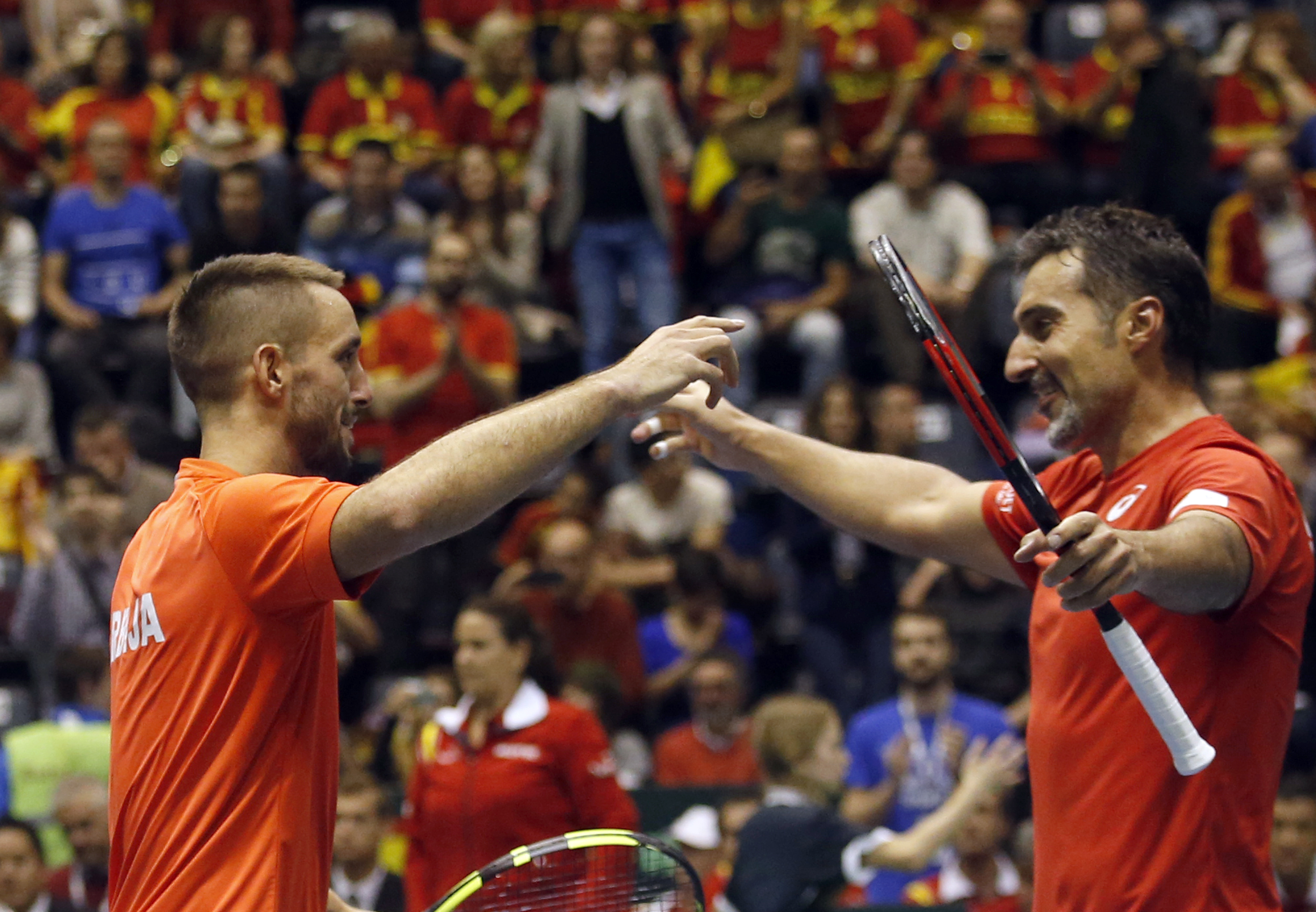 Serbia's Nenad Zimonjic, right, and his partner Viktor Troicki celebrate after winning their Davis Cup quarterfinal tennis doubles match against Spain's Pablo Carreno Busta and Marc Lopez, in Belgrade, Serbia, Saturday, April 8, 2017. (AP Photo/Darko Voji
