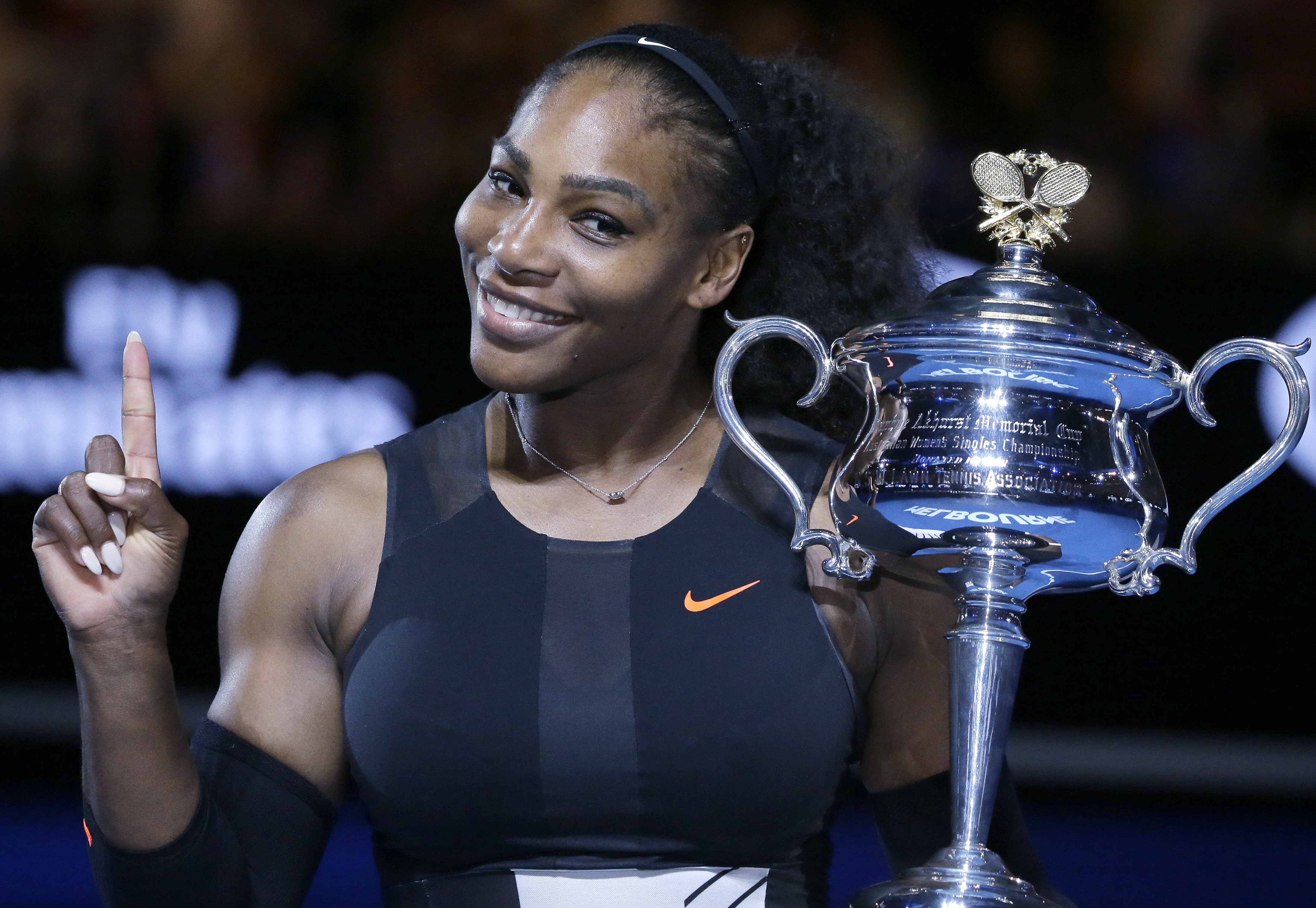 FILE - In this Jan. 28, 2017, file photo, Serena Williams holds up a finger and her trophy after defeating her sister, Venus, in the women's singles final at the Australian Open tennis championships in Melbourne, Australia. A spokeswoman for Williams says